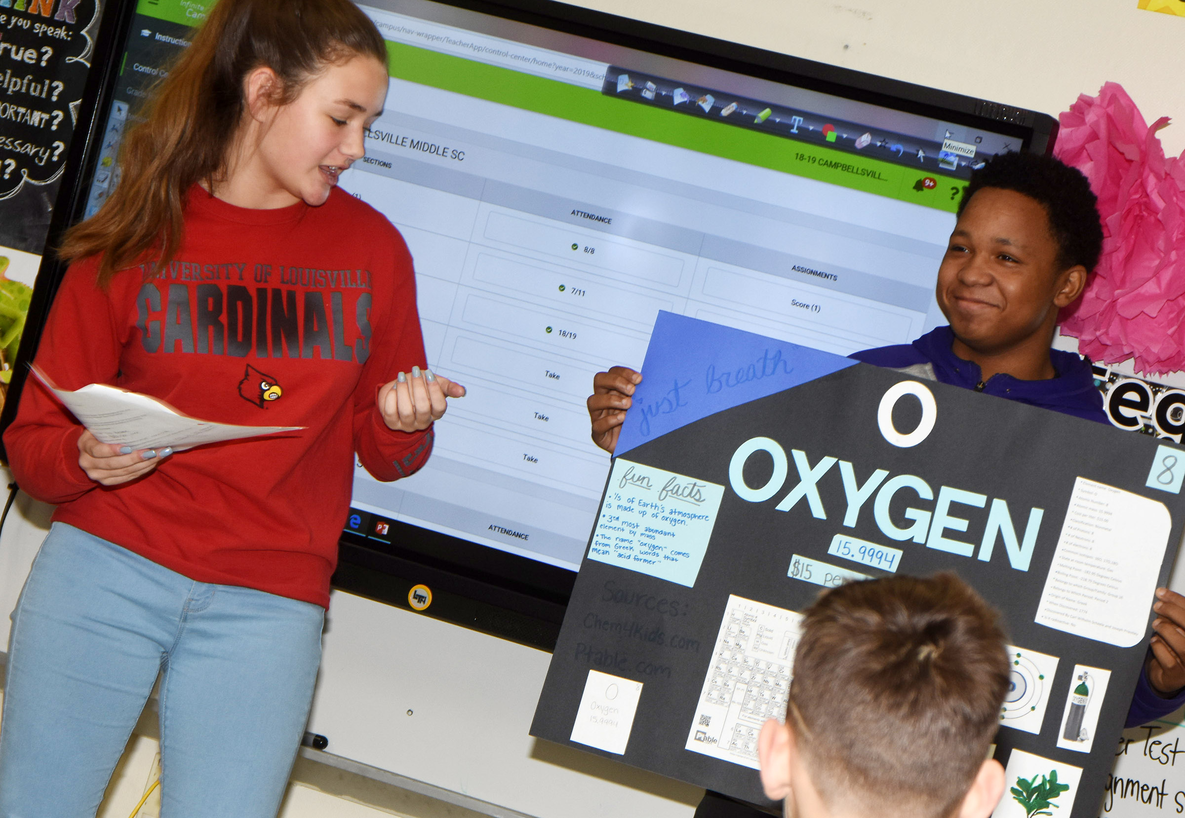 CMS eighth-graders Haylee Allen delivers her presentation about oxygen as classmate Deondre Weathers holds her poster.