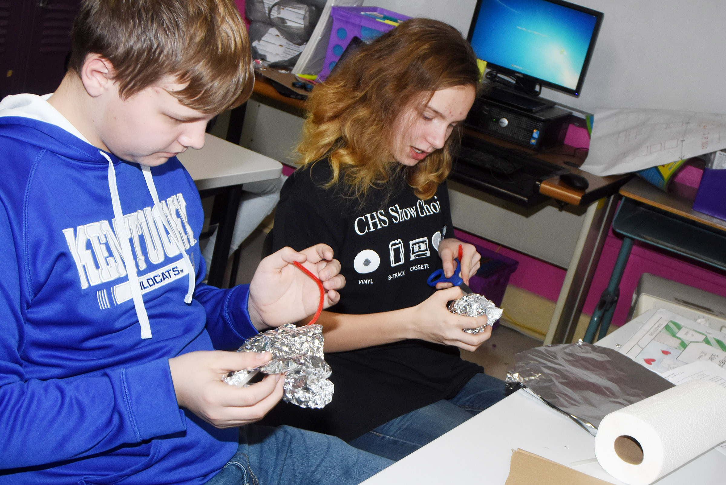 CMS seventh-grader Hunter Falls, at left, and eighth-grader Adrianna Sluder use tinfoil and pipe cleaners to make their invention.