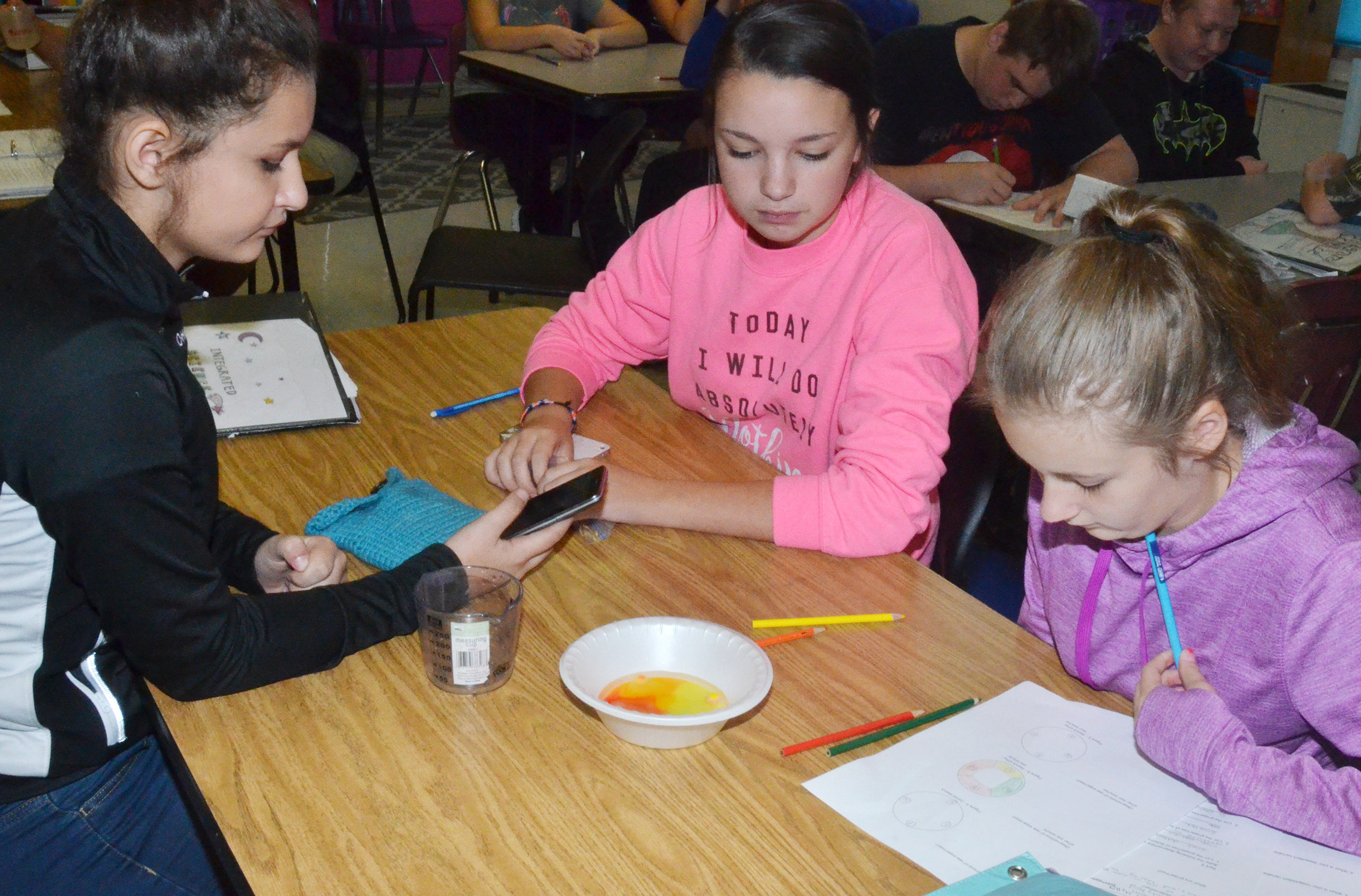 CMS eighth-graders, from left, Christina Miller, Karley Morris and Serenity Ford perform their lab exercise.