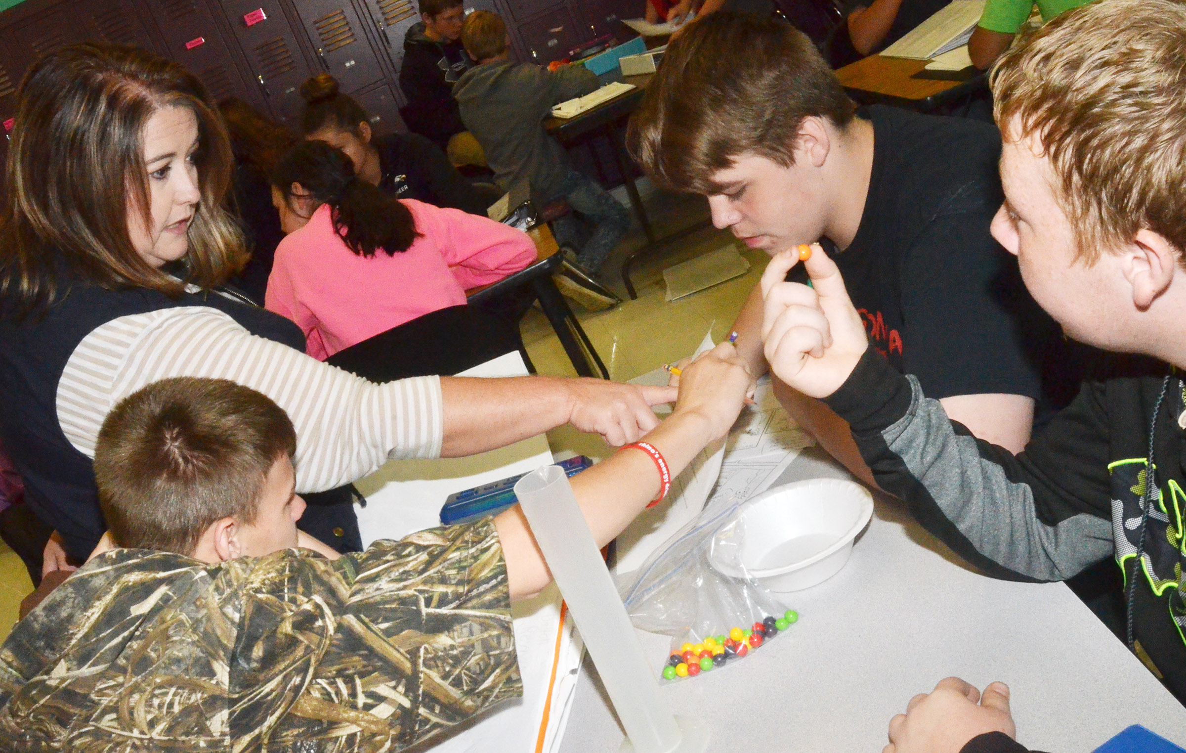 CMS teacher Amy Knifley helps eighth-grade students, from left, Dalton Reynolds, Austin Jeffries and Ryan Milburn as they perform their lab exercise.