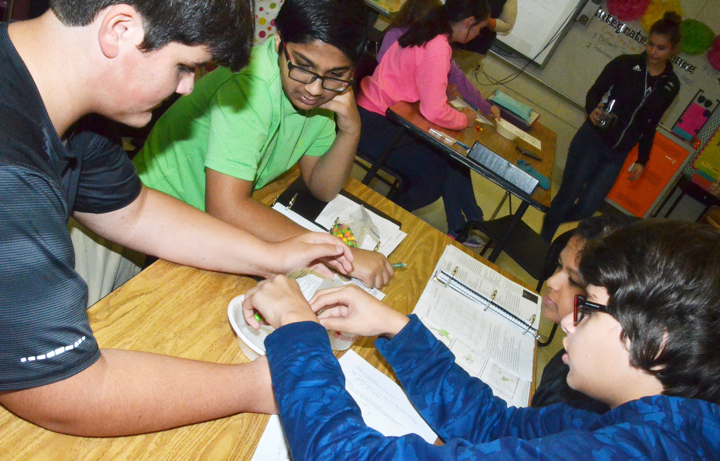 CMS eighth-graders, from left, Logan Rakes, Yash Patel, Tezon Mitchell and Nate Arachi perform their experiment.