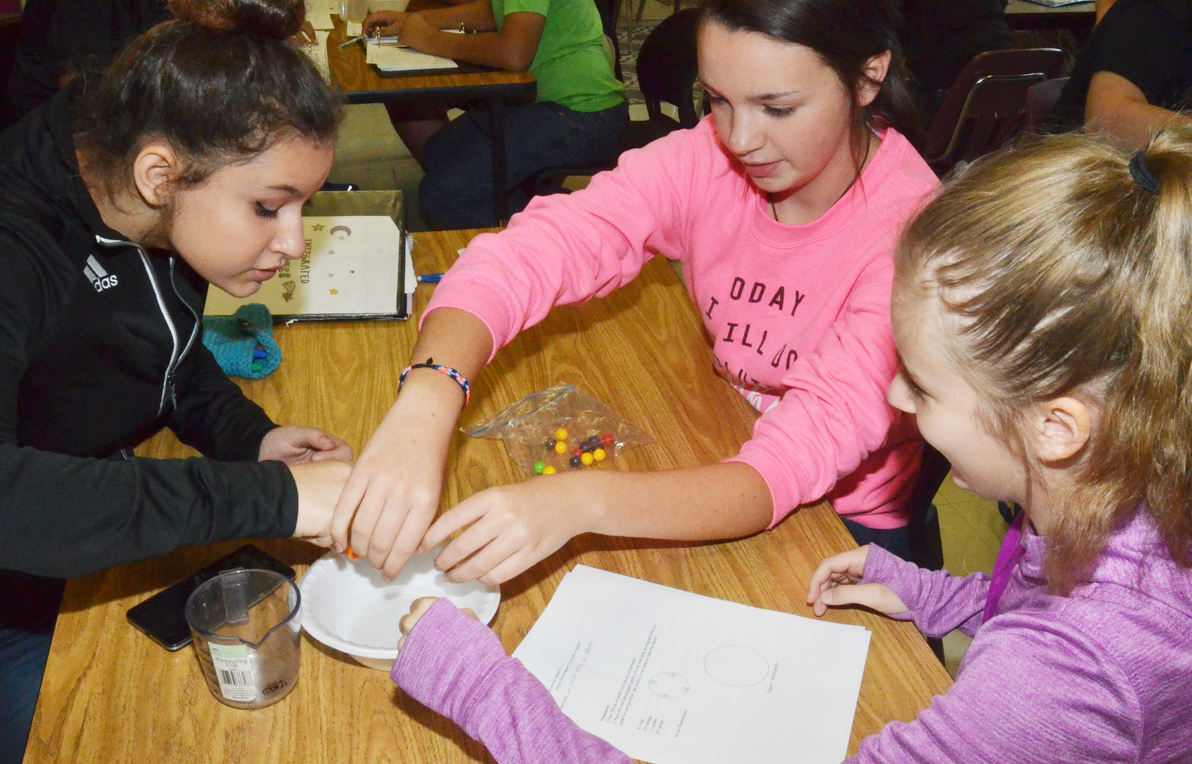 CMS eighth-graders, from left, Christina Miller, Karley Morris and Serenity Ford perform their experiment.