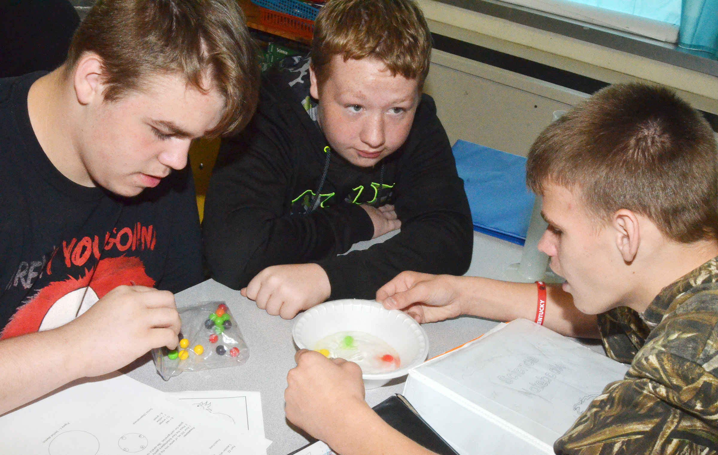 CMS eighth-graders, from left, Austin Jeffries, Ryan Milburn and Dalton Reynolds watch to see what happens to their Gobstopper candies.
