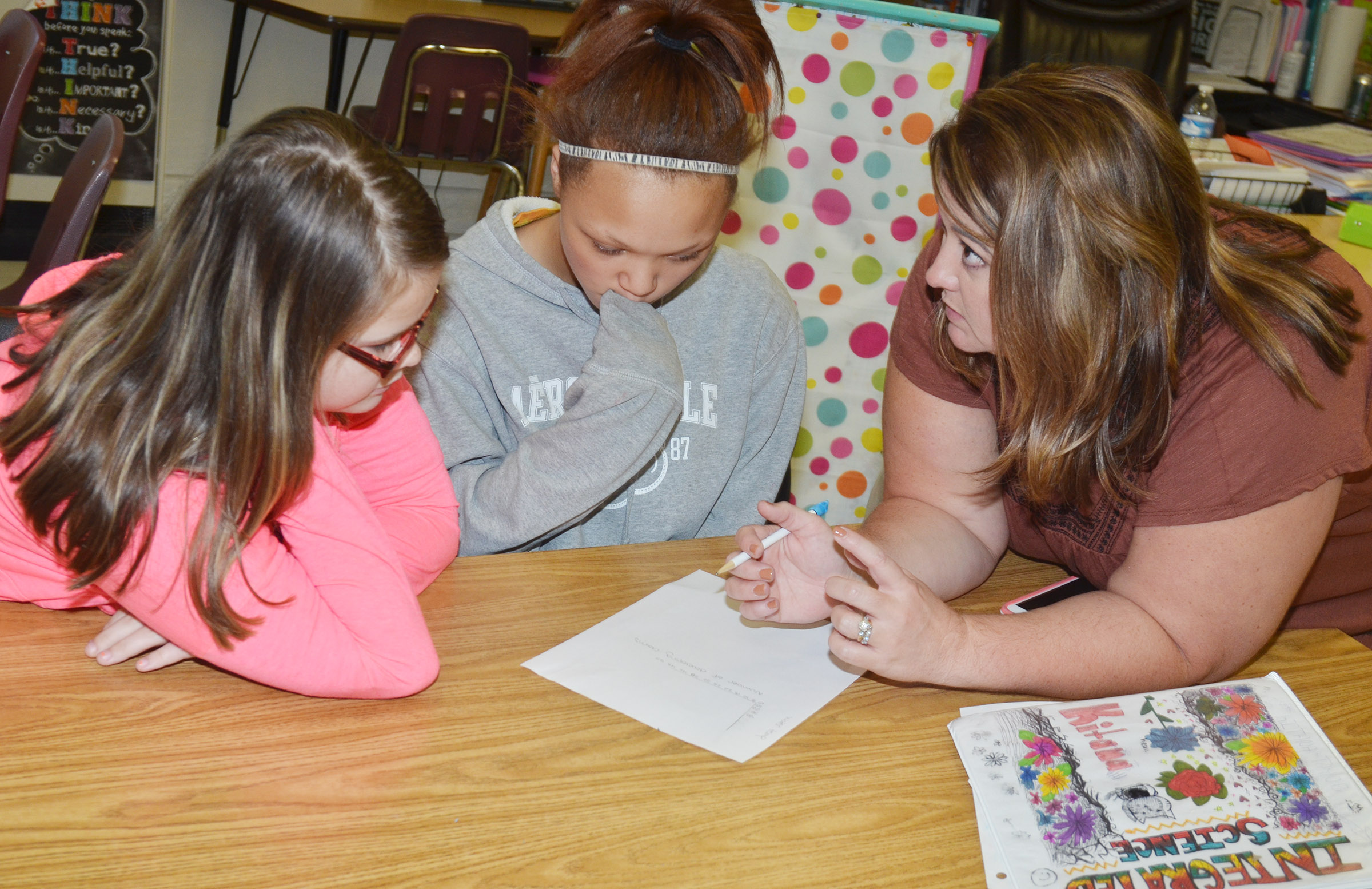 CMS eighth-graders Xierra Underwood, at left, and Kitana Taylor talk to teacher Amy Knifley about their graph.