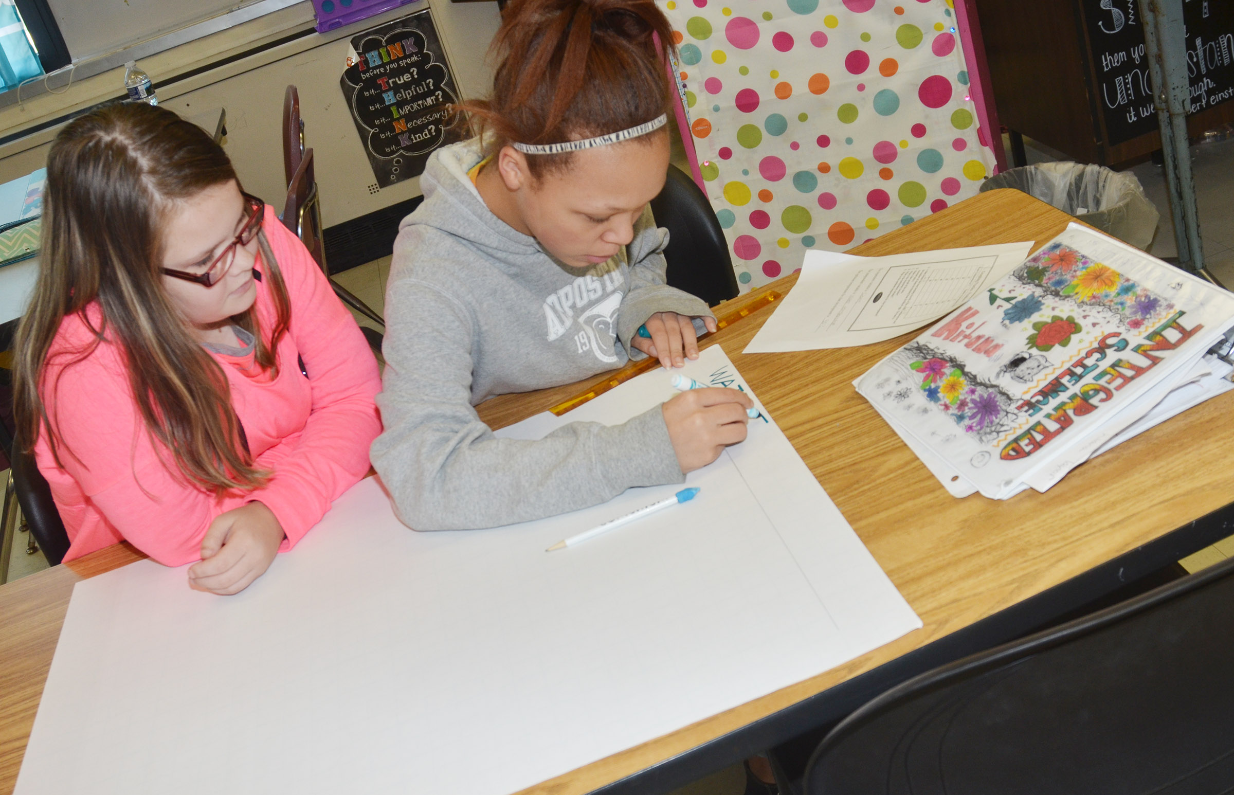 CMS eighth-graders Xierra Underwood, at left, and Kitana Taylor make their graph.