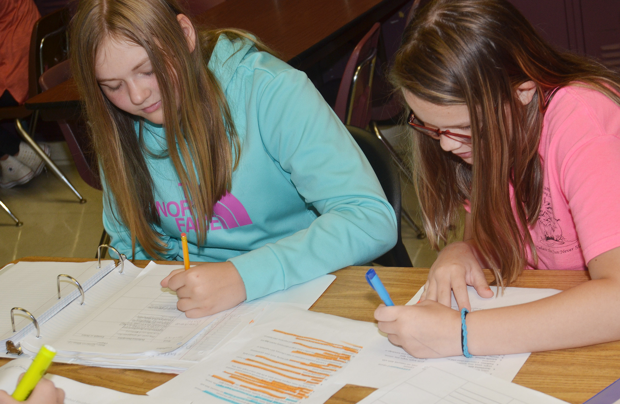 CMS eighth-graders Isabella Vannice, at left, and Xierra Underwood write their science definitions.
