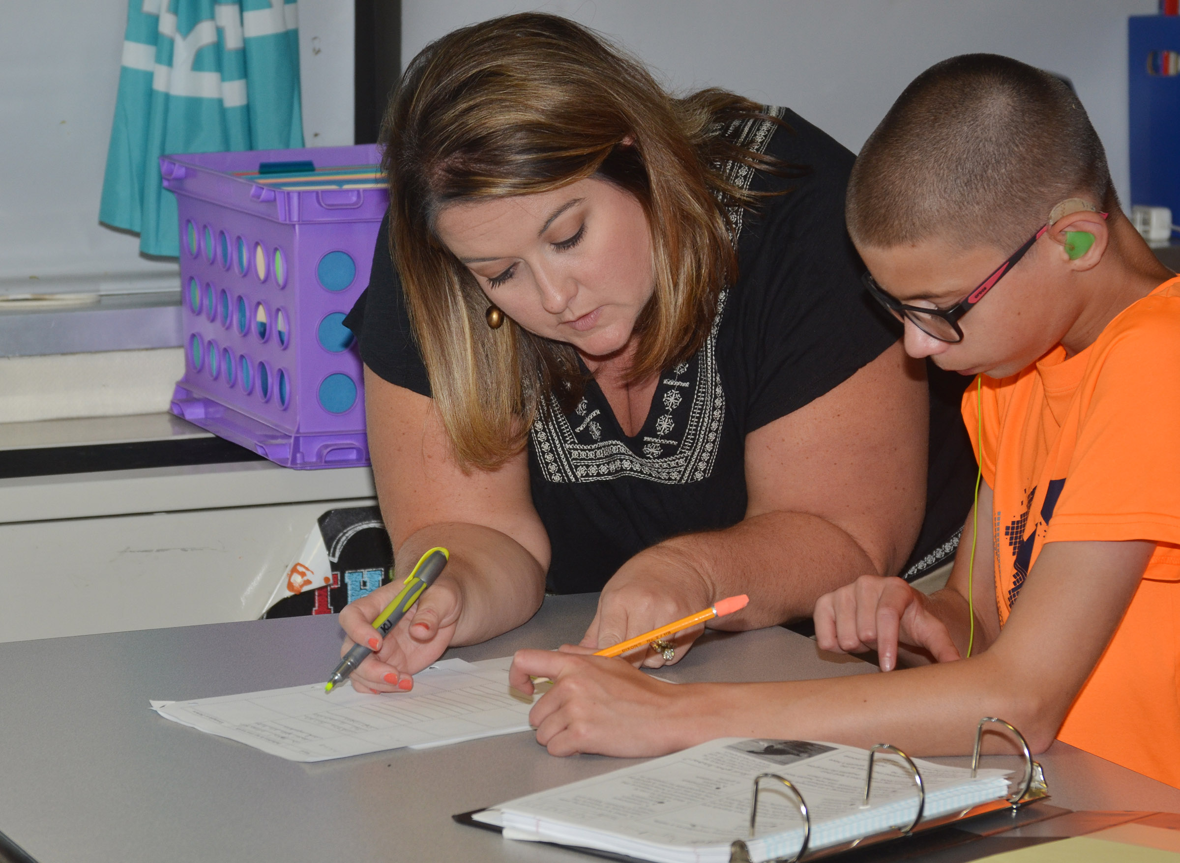 CMS teacher Amy Knifley helps eighth-grader Grant Lawson with a definition.