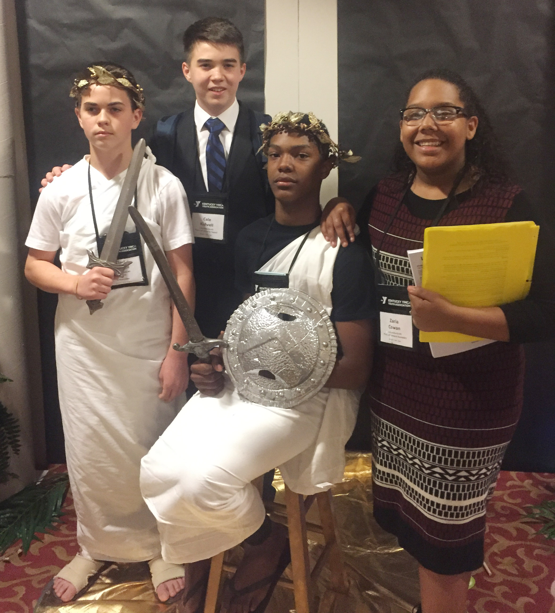 CMS eighth-graders Clark Kidwell and Zaquan Cowan, in front, dress for the school's Greece presentation with CHS freshmen Cole Kidwell and Zaria Cowan, who served in leadership roles at KUNA. Cowan was president of the United Nations General Assembly, and Kidwell served as president of the Security Council.