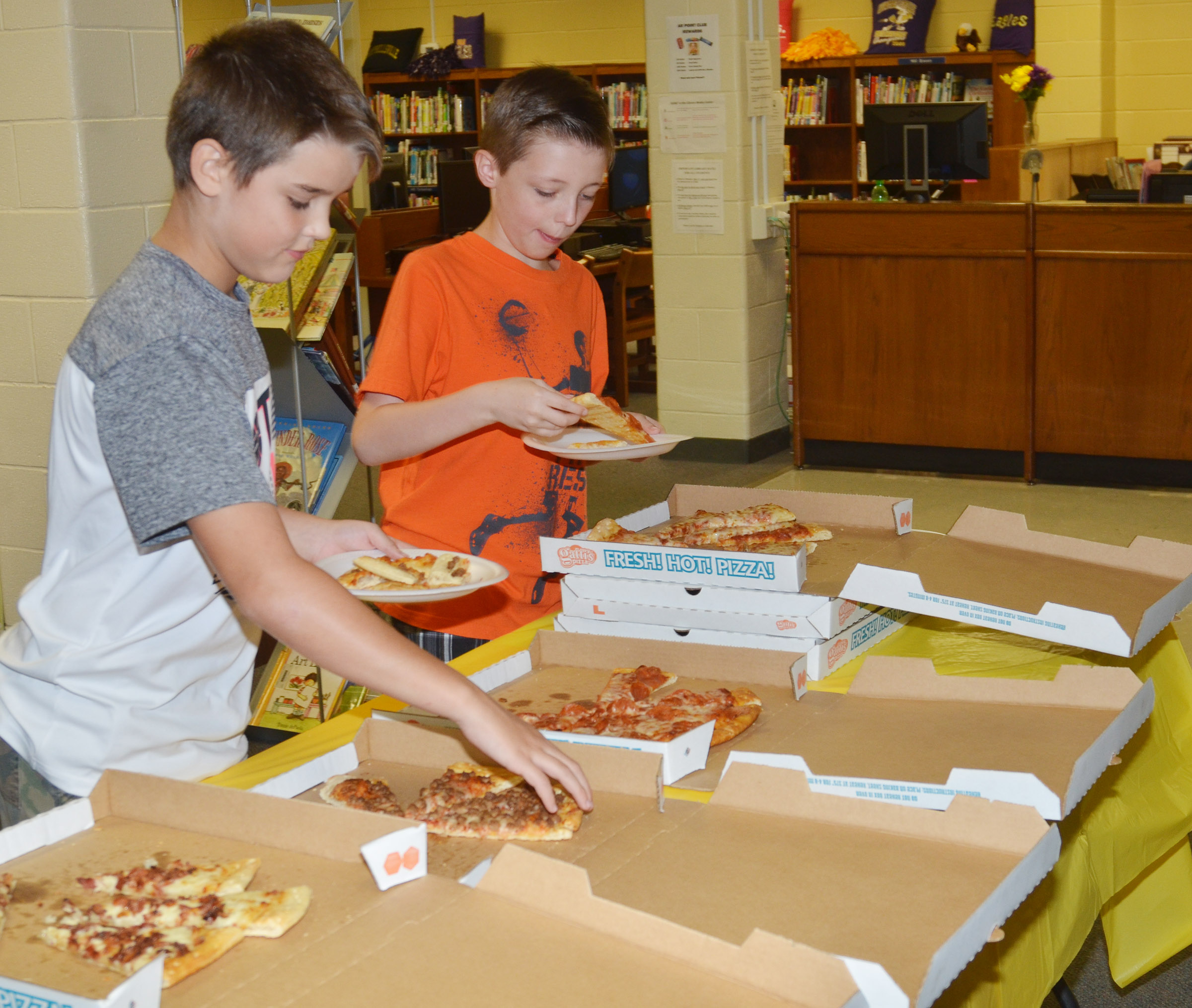CMS fifth-grader Kaden Bloyd, at left, and fourth-grader Jaxon Garrett enjoy a pizza lunch.