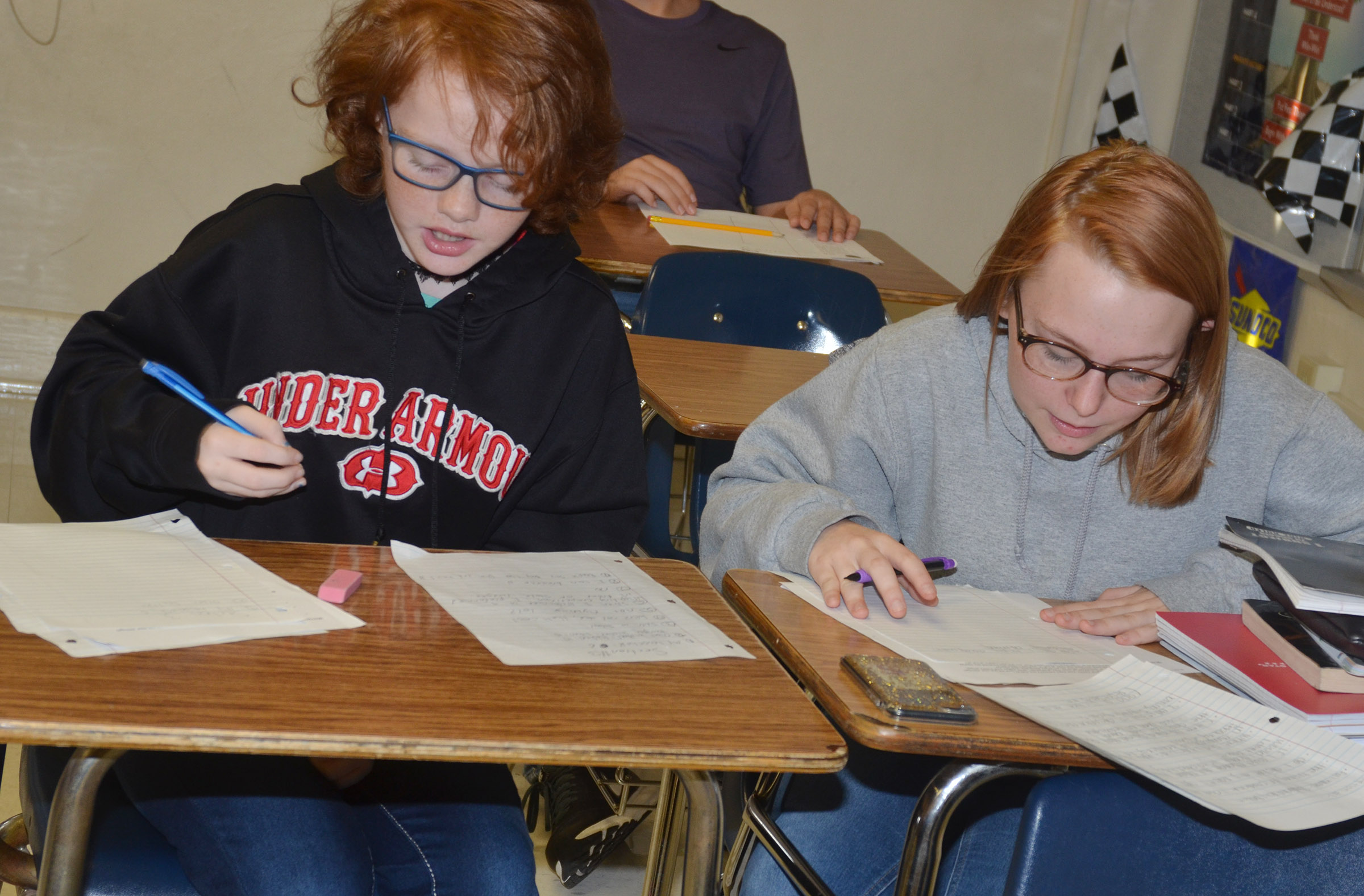 CMS seventh-graders Haley Gutierrez, at left, and Savanna Brown work on their autobiographical assignment.