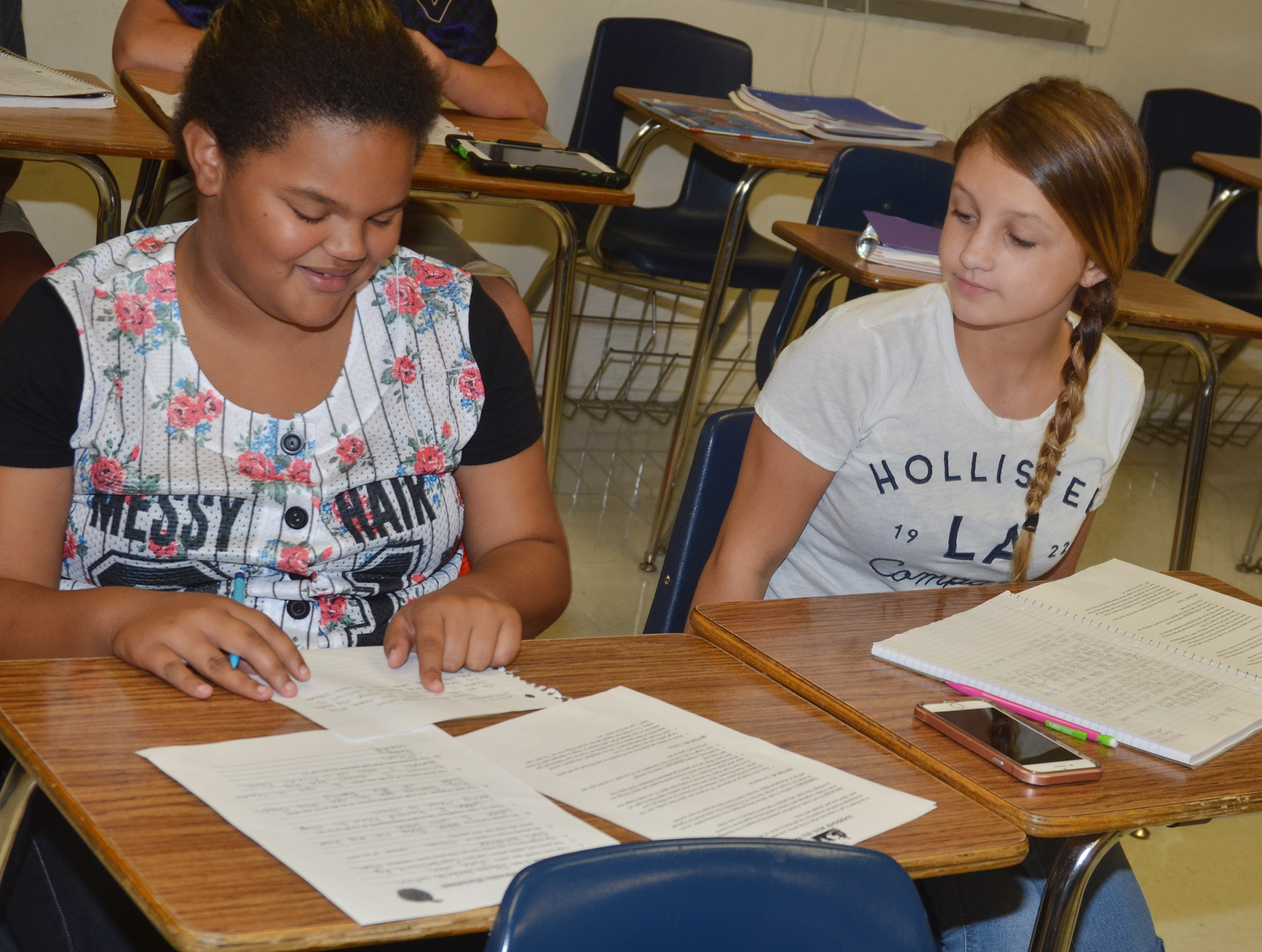 CMS seventh-graders Alissa Lofton, at left, and Alexis Byers work on their autobiographical assignment.