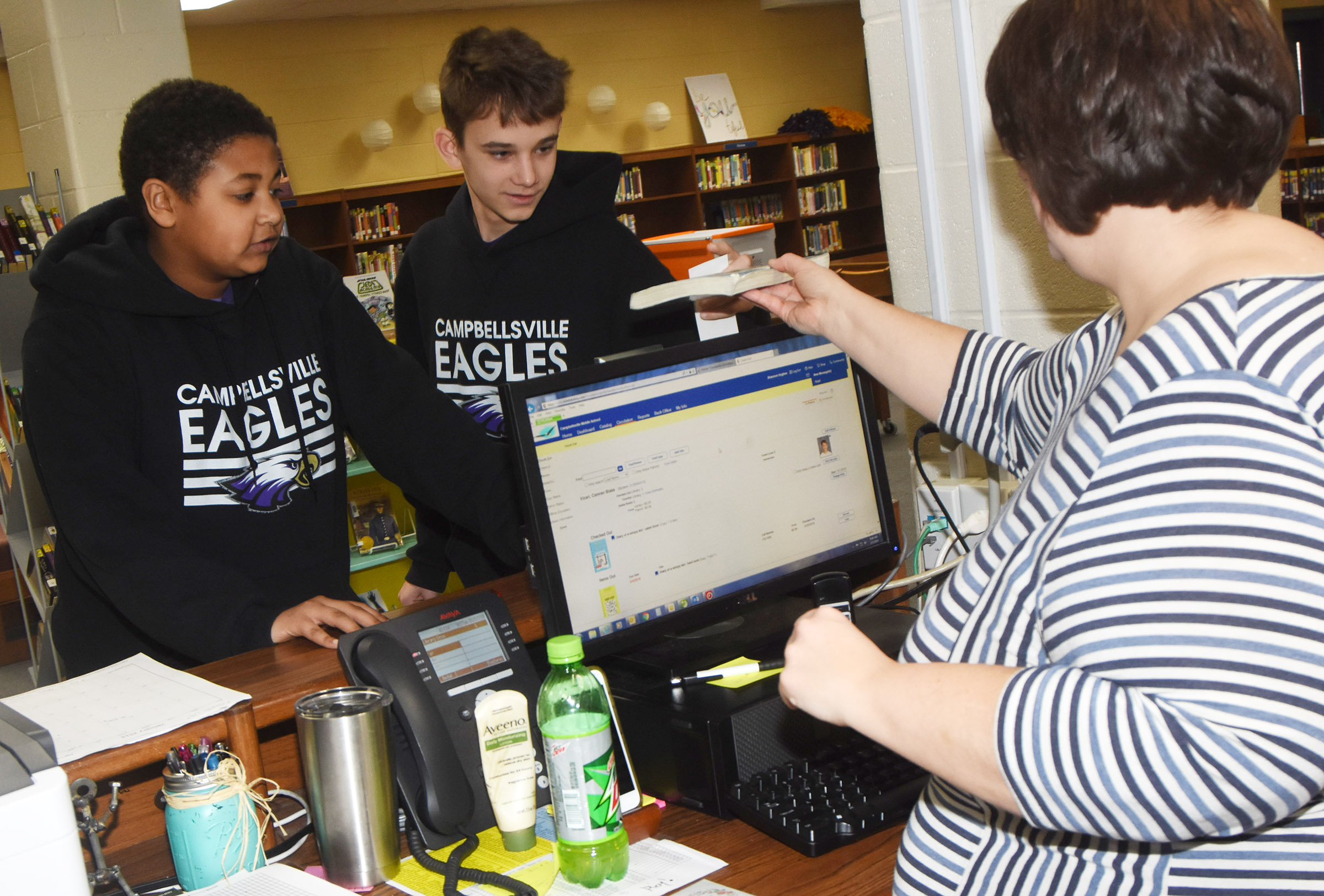 CMS eighth-graders Ronin Smith, at left, and Camren Vicari check out books with media specialist Shannon Hughes.