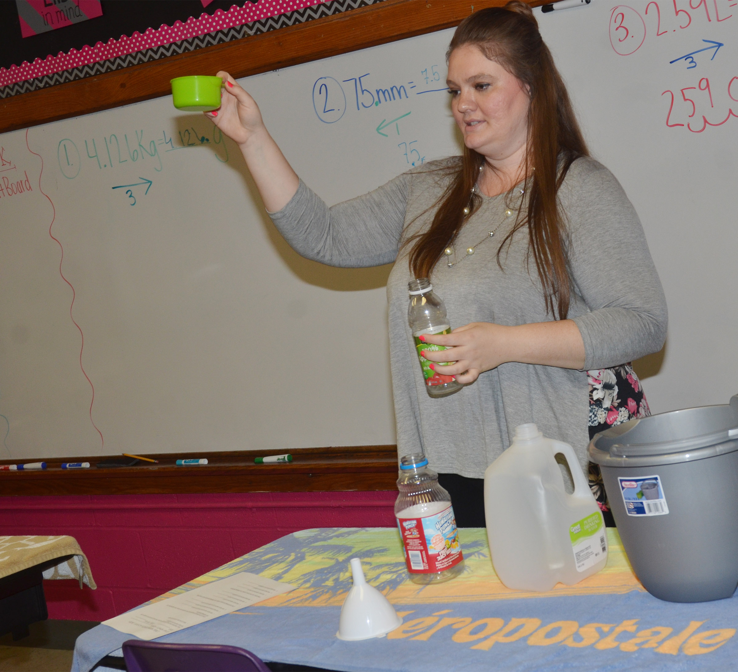CMS fifth-grade teacher Ann Michael Tucker shows students how to convert liquid measurements.