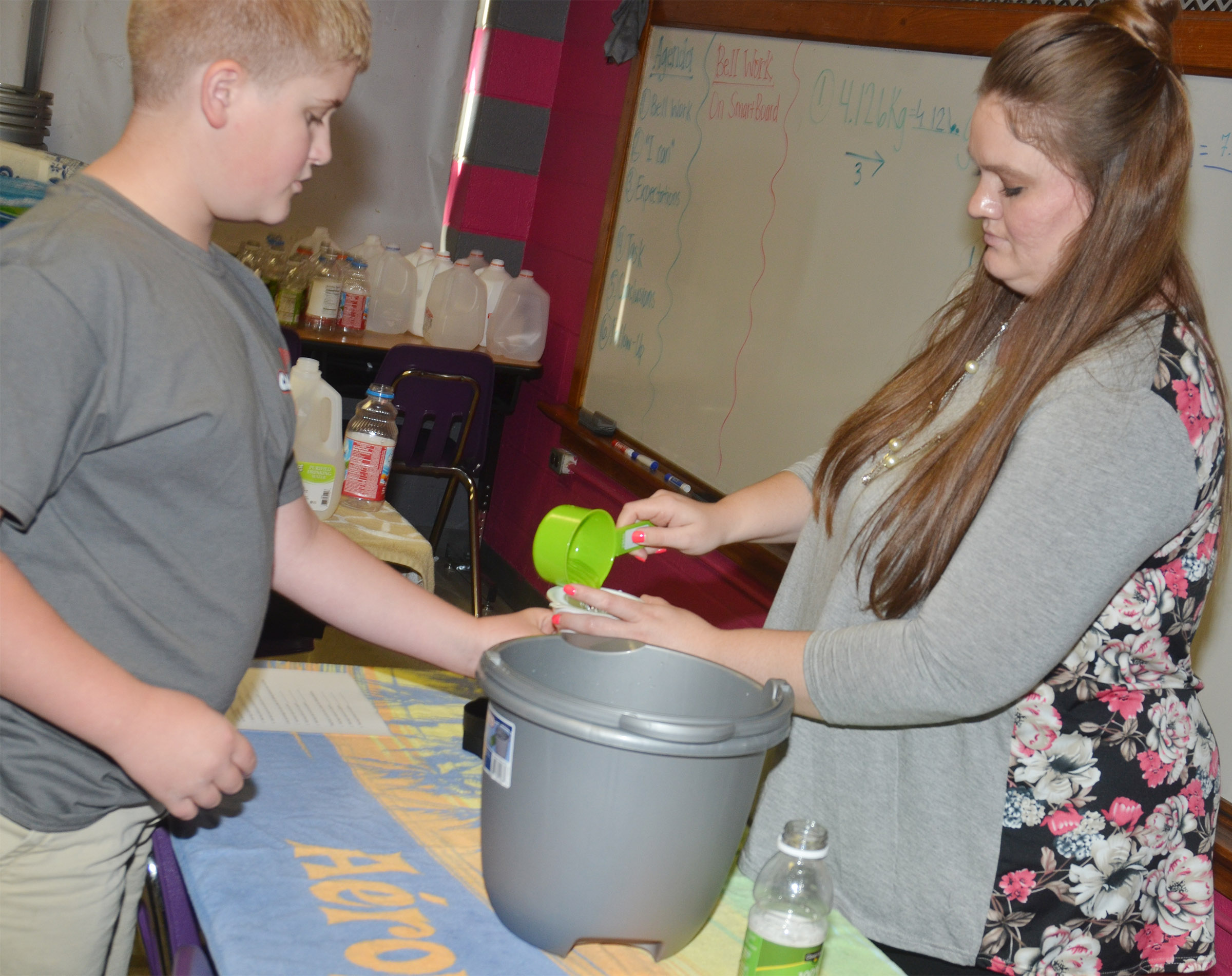 CMS fifth-grader Lance Knifley practices converting liquid measurements with teacher Ann Michael Tucker.
