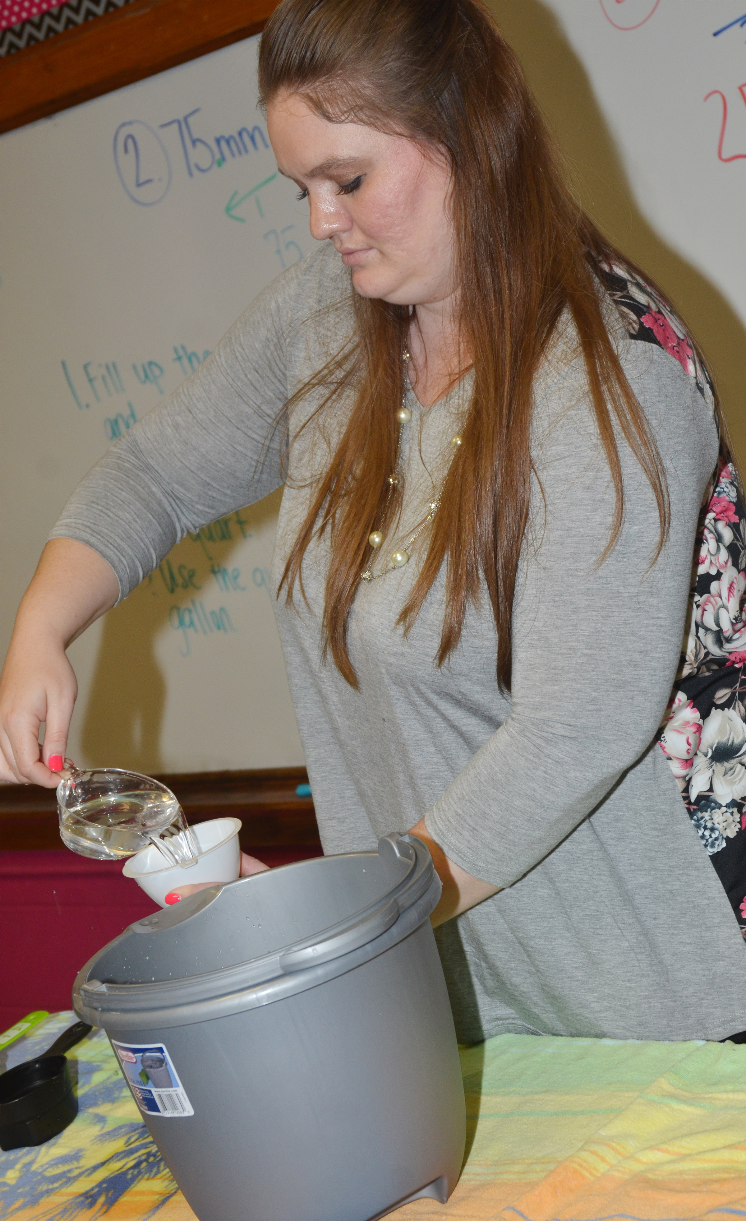 CMS fifth-grade teacher Ann Michael Tucker measures water.