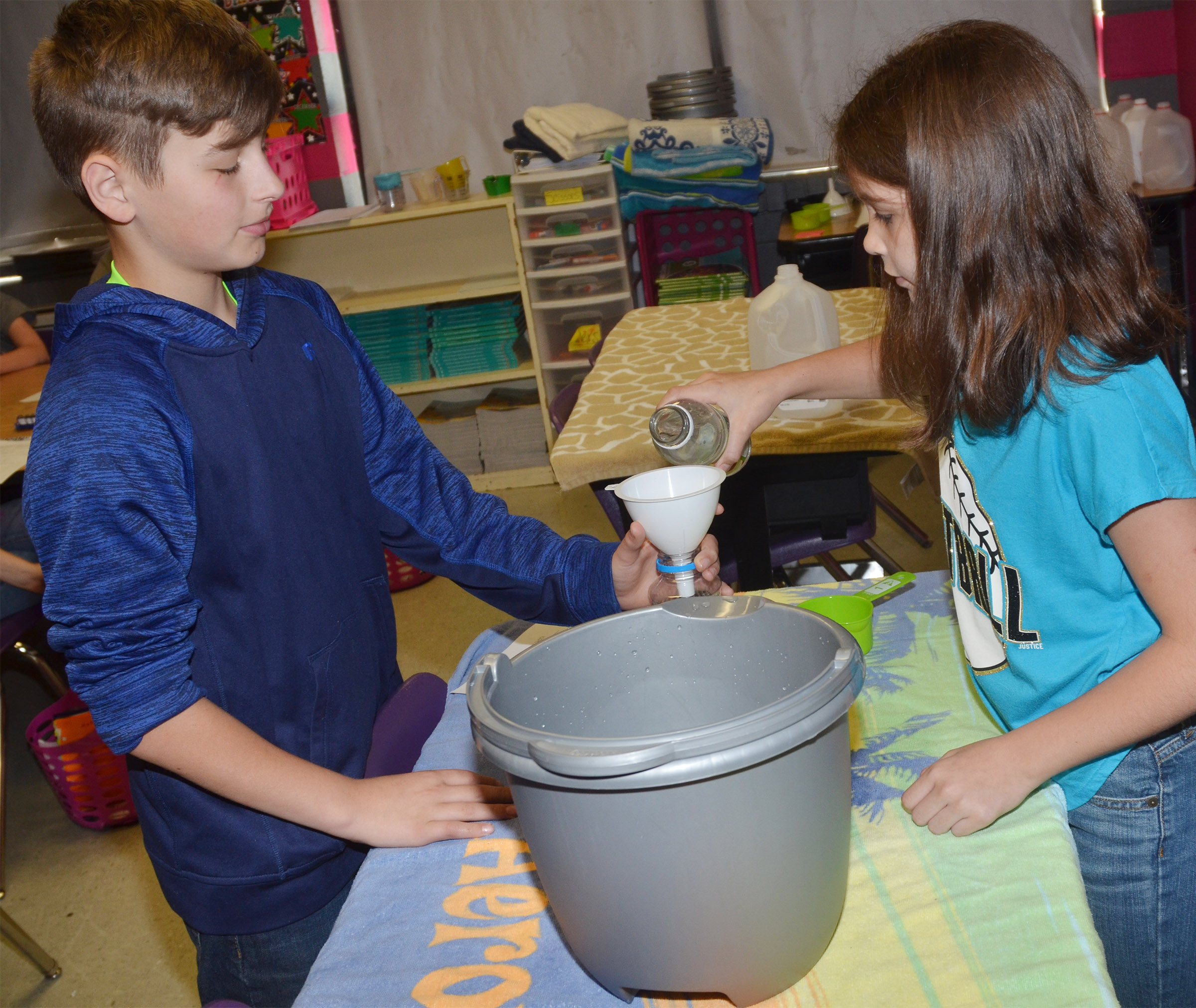 CMS fifth-graders Jaxon Sidebottom, at left, and Makayla Dudley practice measuring liquids.