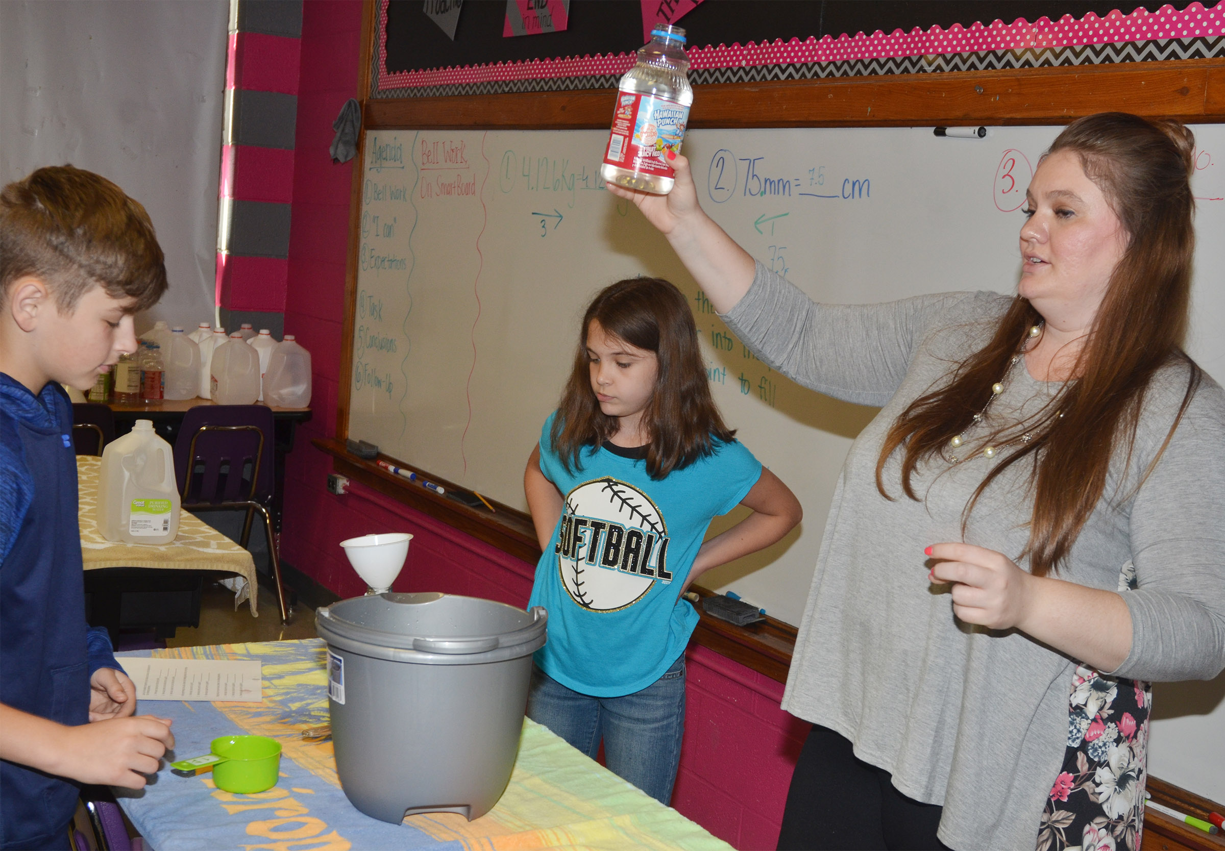 CMS fifth-grade teacher Ann Michael Tucker helps students Jaxon Sidebottom, at left, and Makayla Dudley measure liquids.