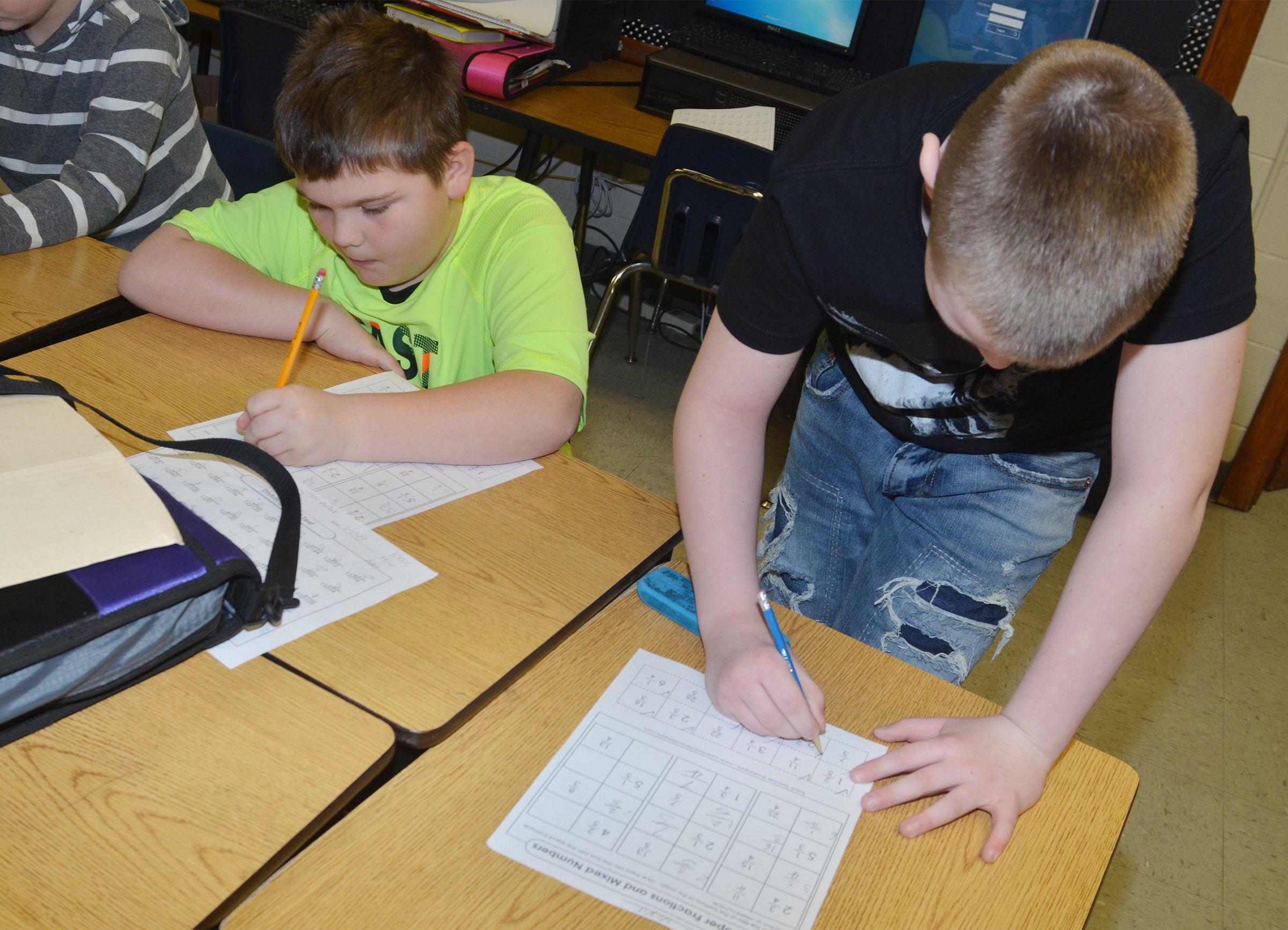CMS fifth-graders Logan England, at left, and Kaleb Miller work to convert fractions to mixed numbers.