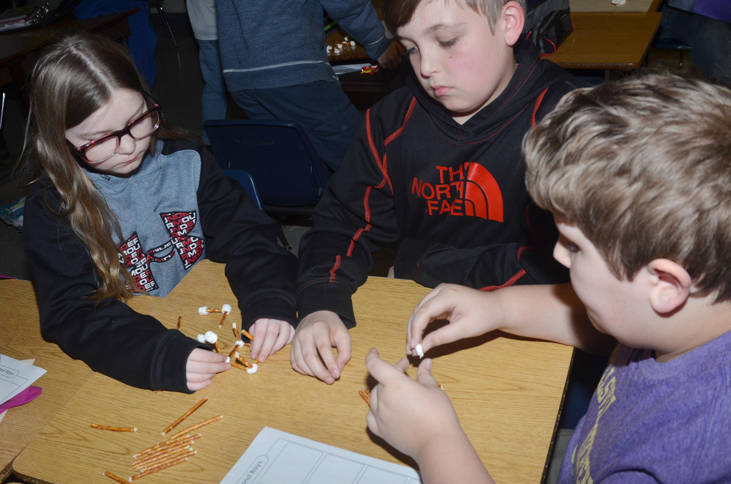 From left, CMS fourth-graders Morgan Spears, Skylar Wilhoite and Zeke Harris make geometric shapes with marshmallows and pretzels.