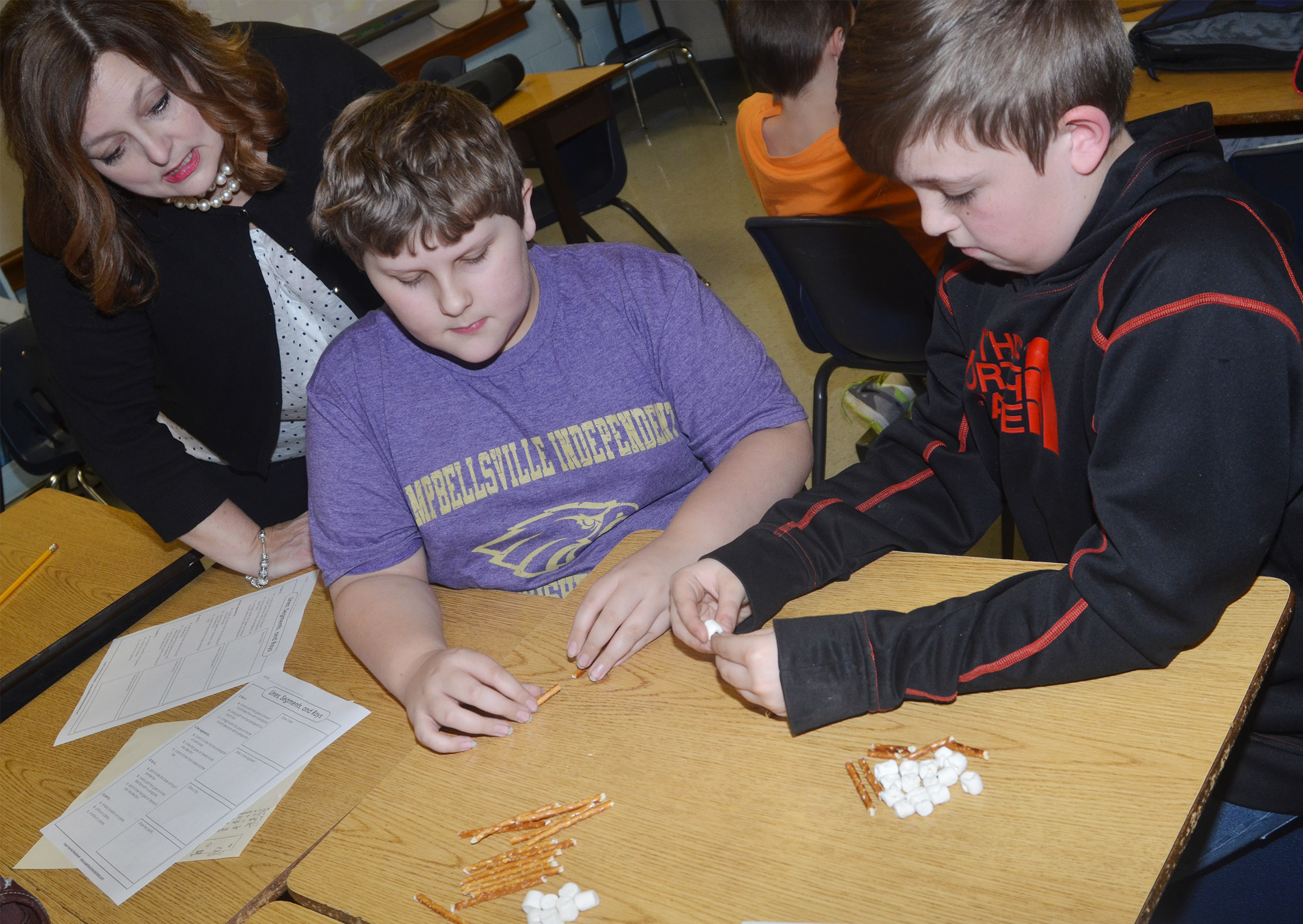 CMS fourth-grade teacher Garnetta Murrell helps Zeke Harris, center, and Skylar Wilhoite make geometric shapes with marshmallows and pretzels.
