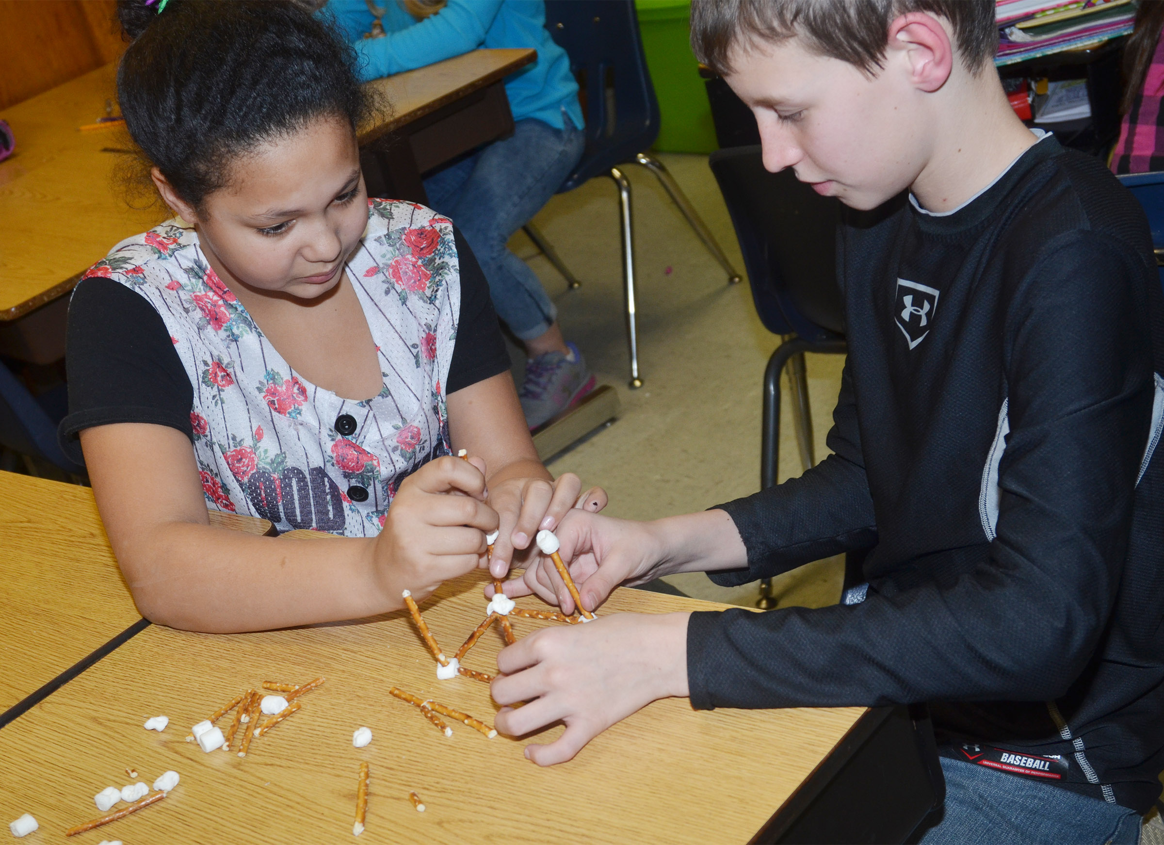 CMS fourth-graders Kenya Bridgewater, at left, and Rowan Petett make geometric shapes with marshmallows and pretzels.