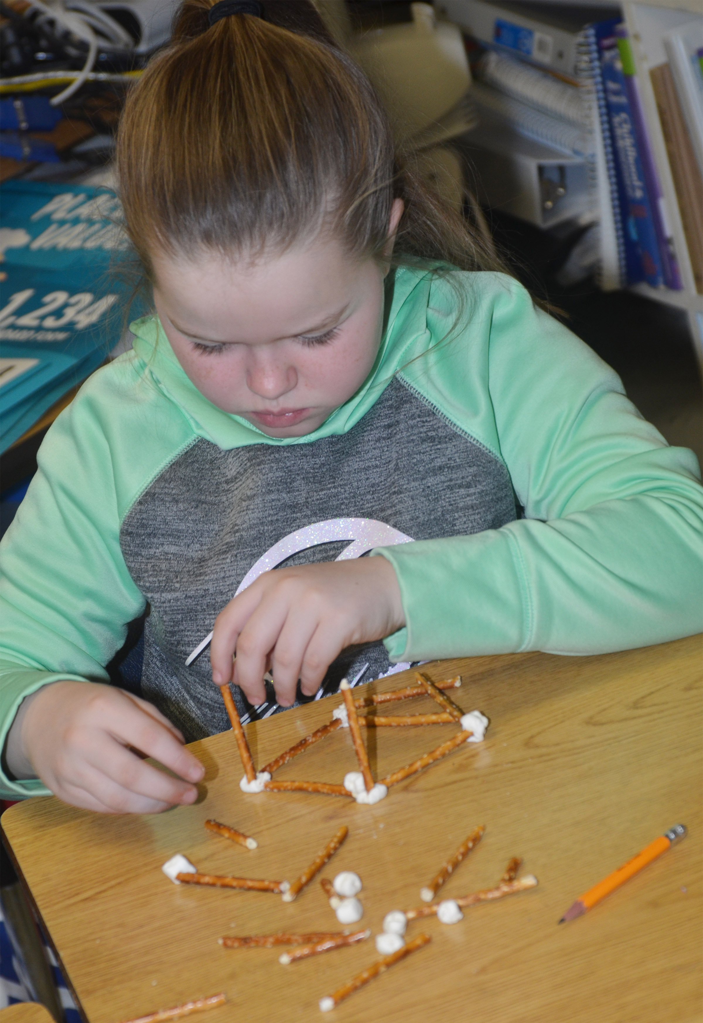 CMS fourth-grader Miley Hash makes a geometric shape out of marshmallows and pretzels.