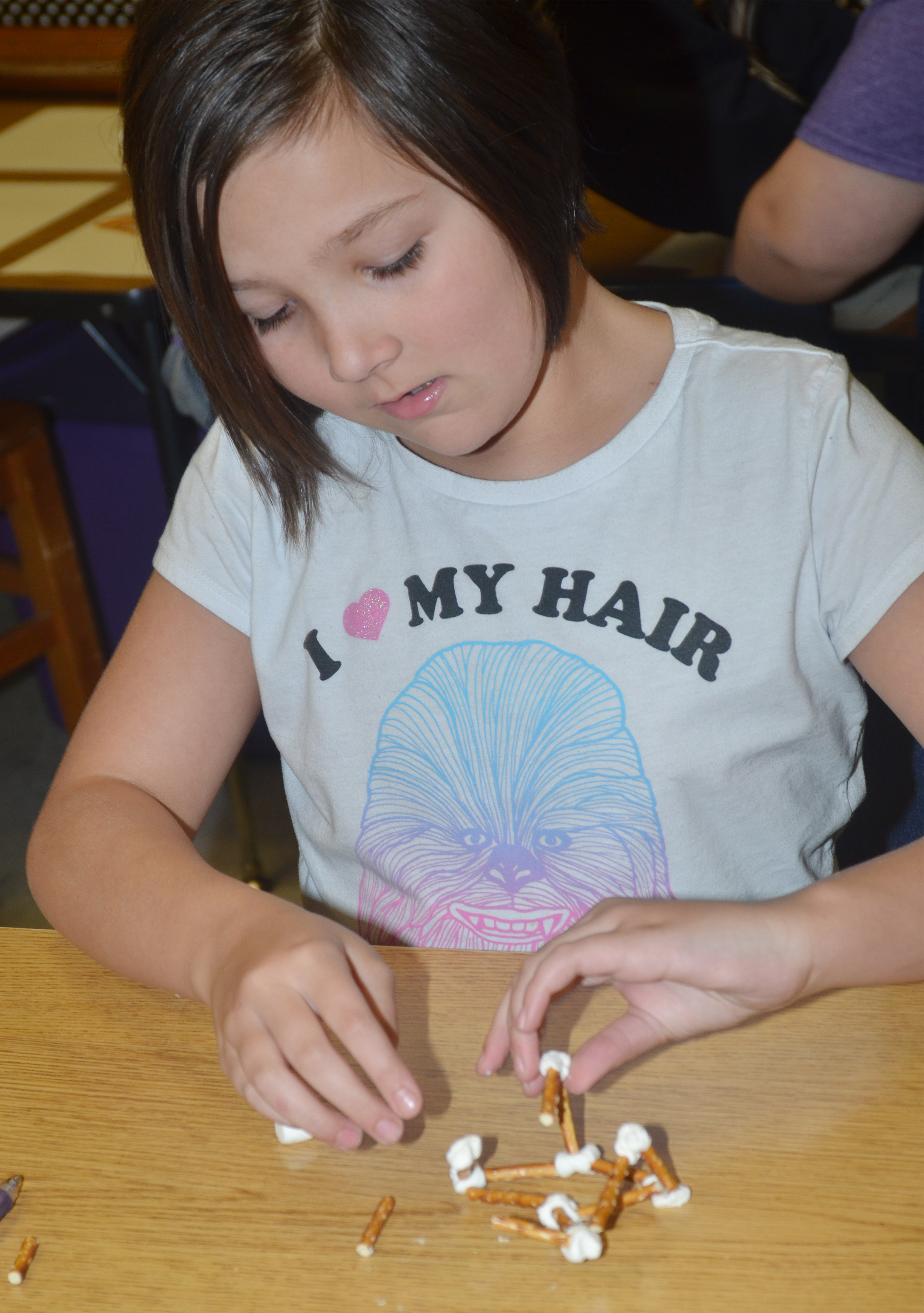CMS fourth-grader Cassie Crick makes a geometric shape out of marshmallows and pretzels.