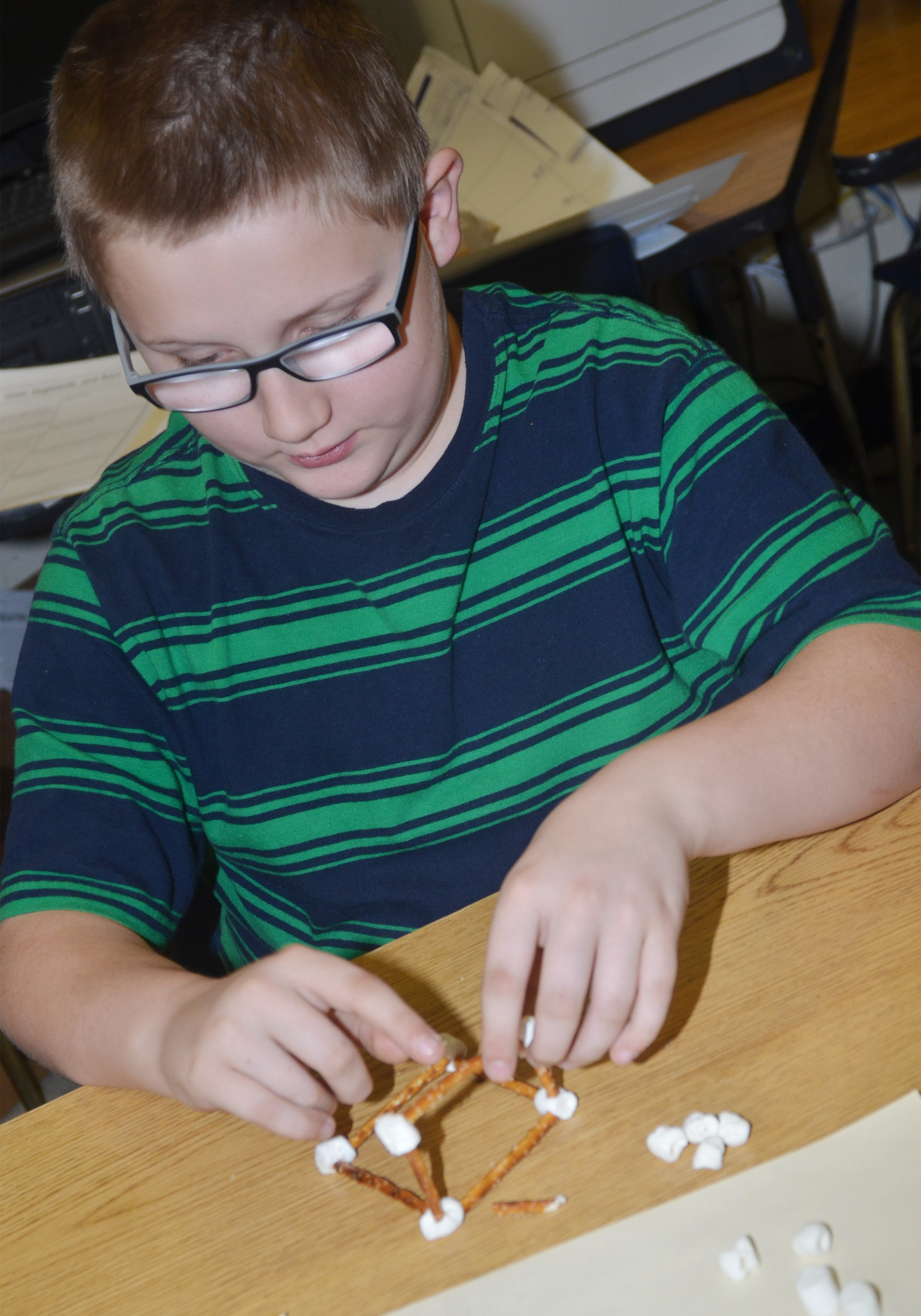 CMS fourth-grader Landon Rakes makes a geometric shape out of marshmallows and pretzels.