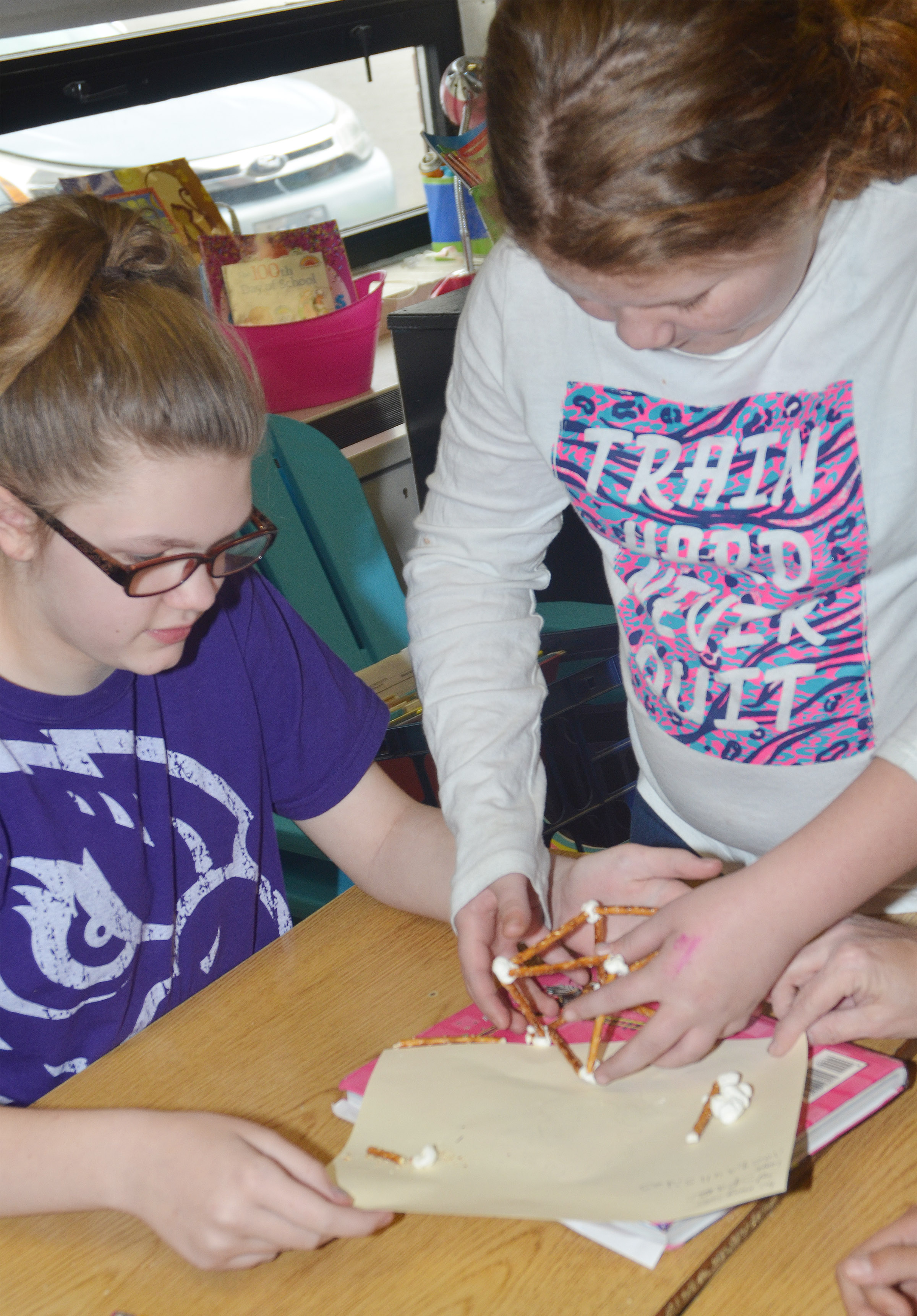 CMS fourth-grader Autumn Jones, at left, and Carmen Gurley make geometric shapes out of marshmallows and pretzels.