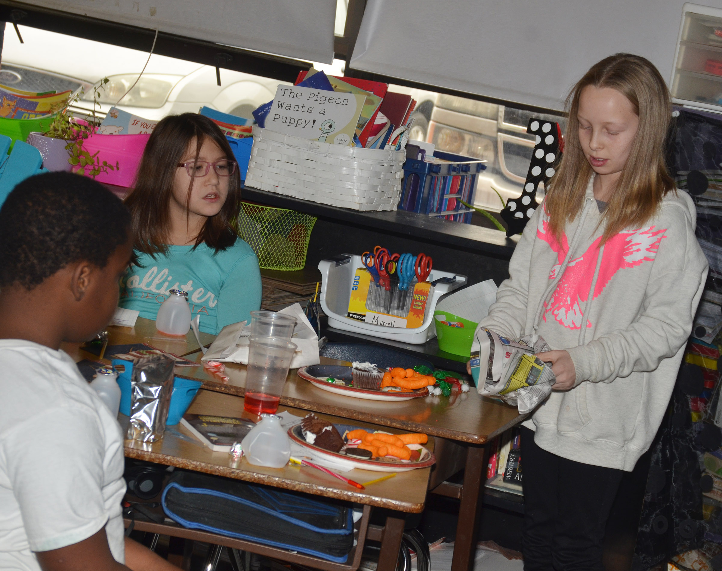 CMS fourth-grader Lily Sallee unwraps her gift.
