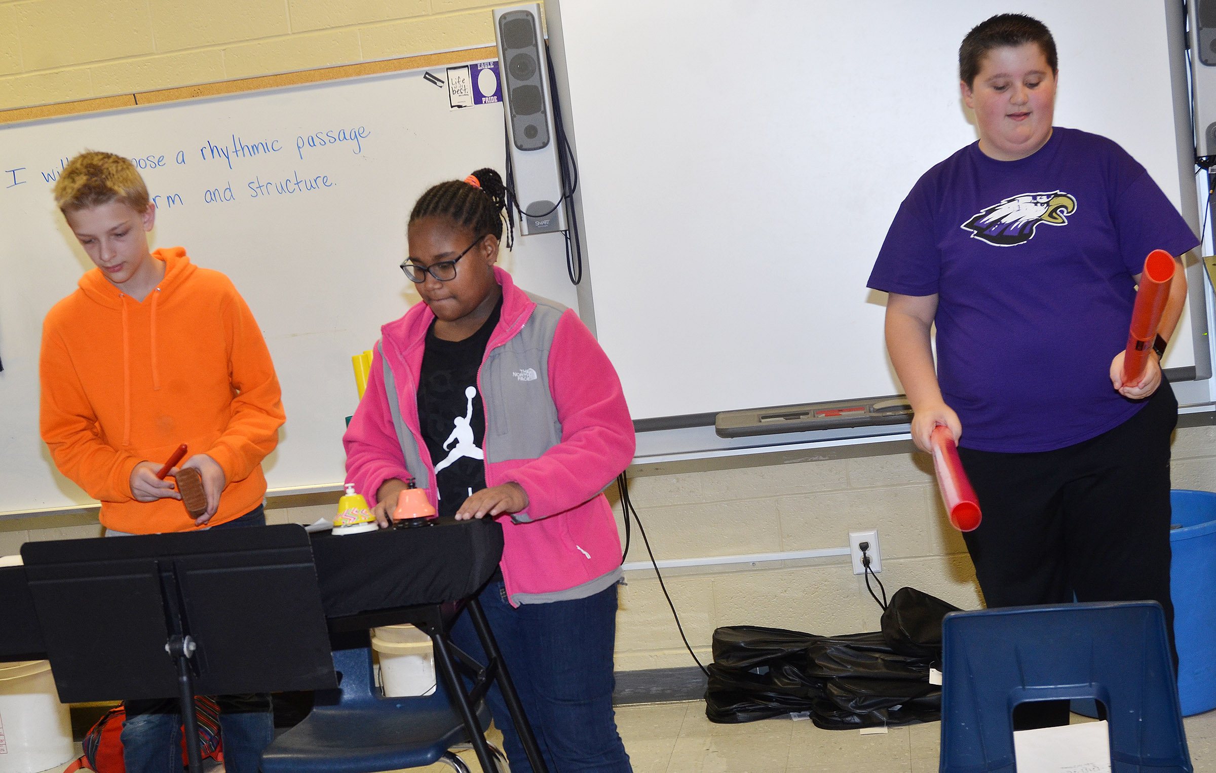 CMS sixth-graders, from left, Jacob Releford, KyAshia Mitchell and Luke McDonald play their original song on the bells, block and boomwhackers.