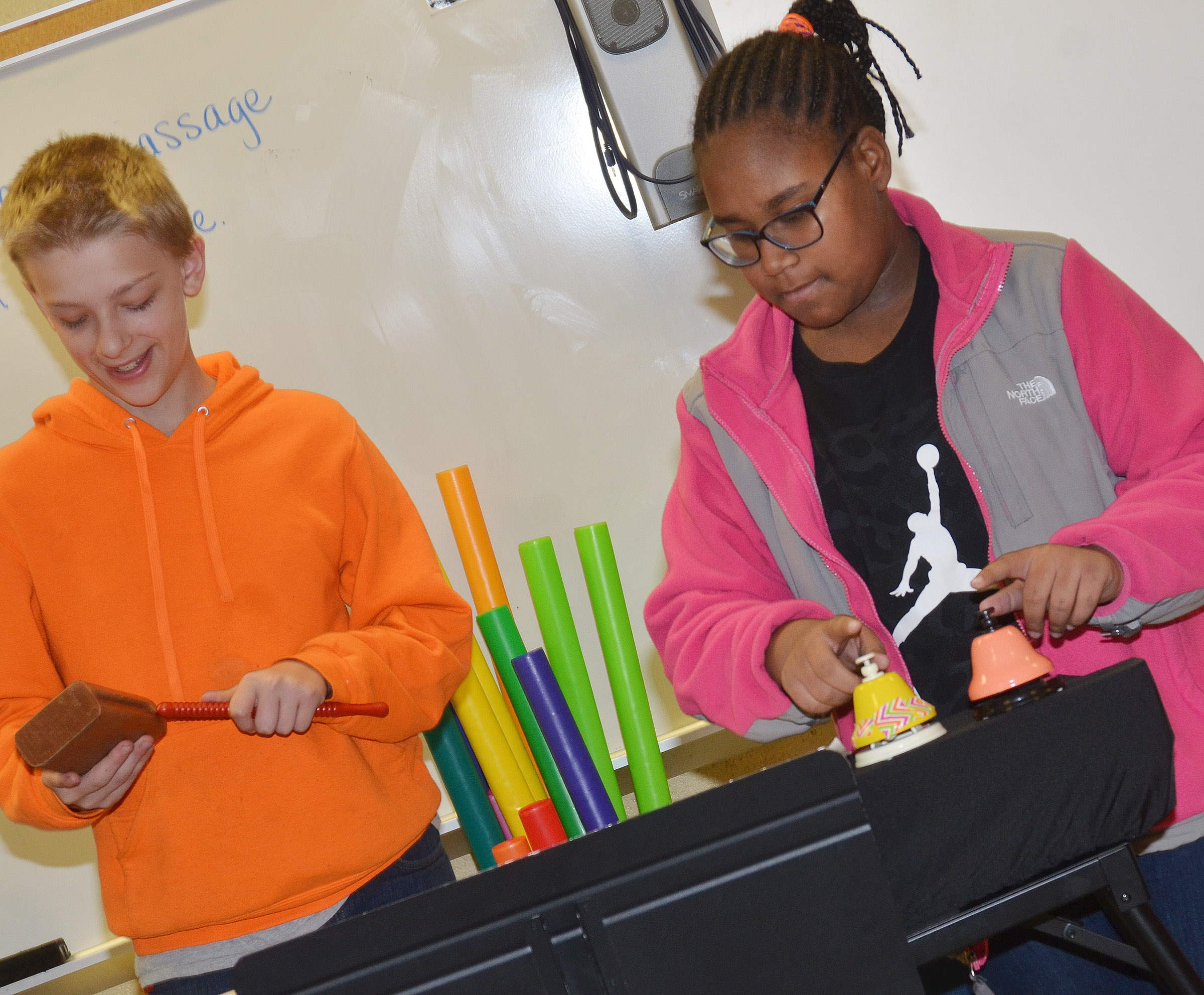 CMS sixth-graders Jacob Releford, at left, and KyAshia Mitchell play their group's original song on the block and bells.