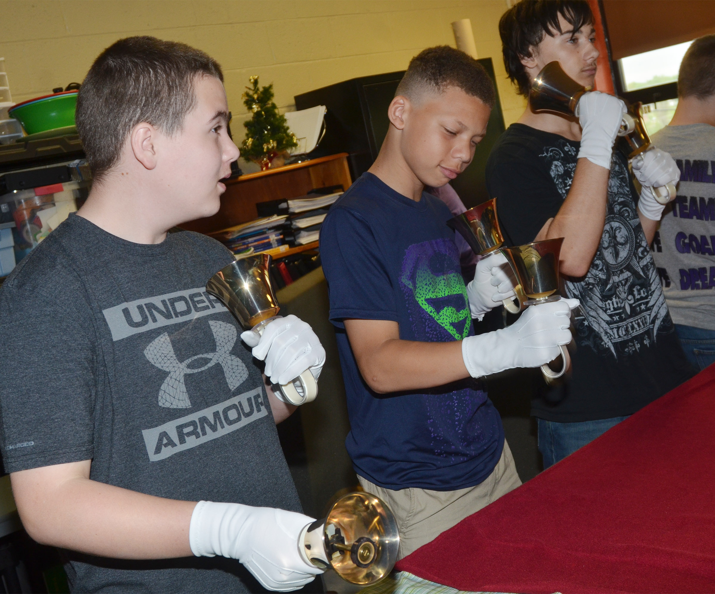 From left, CMS seventh-graders Jack Sabo and Dalvian Thornton and eighth-grader Jonathan Foster play the handbells.