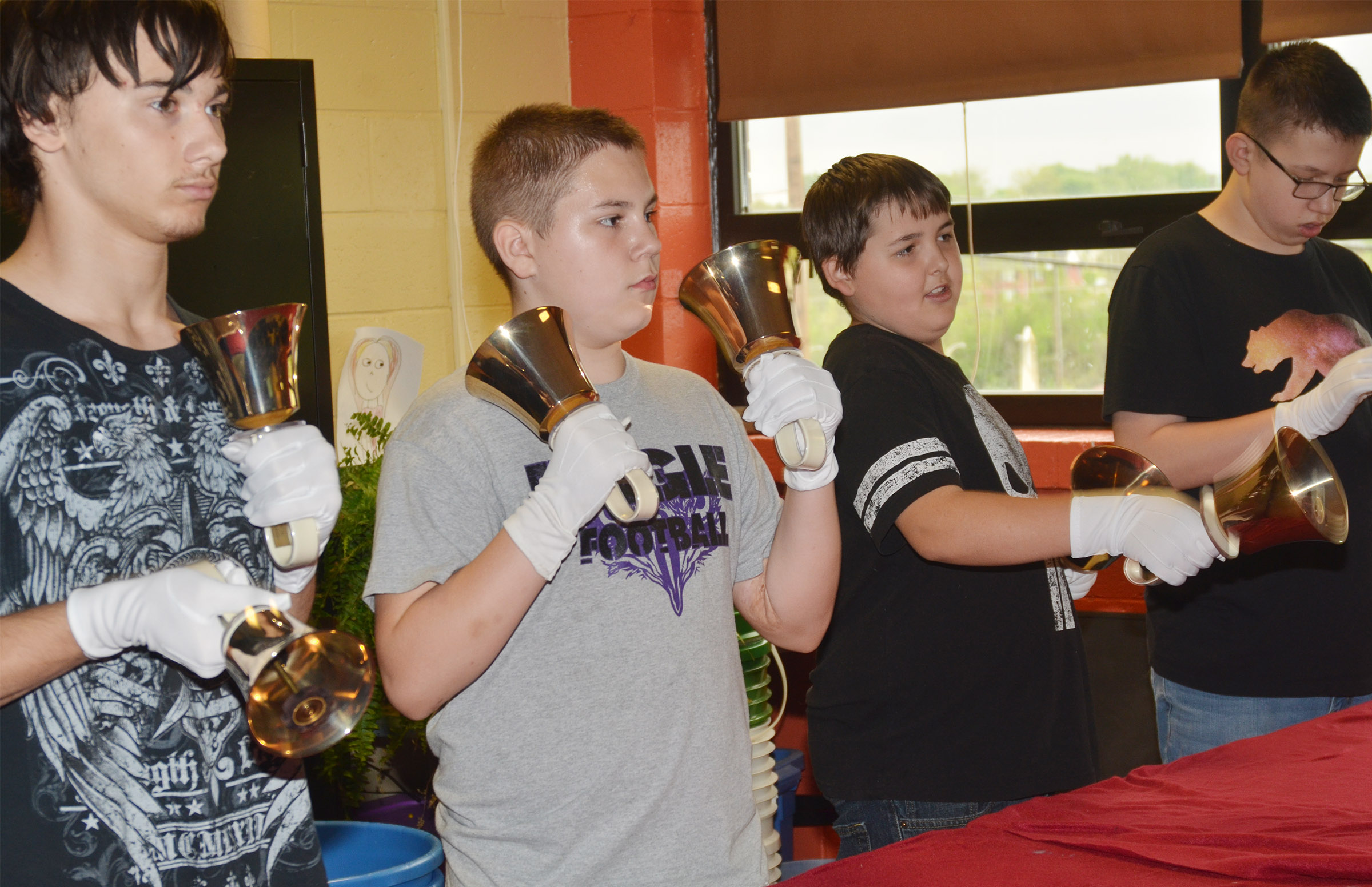From left, CMS eighth-grader Jonathan Foster, fifth-grader Isaac Roddy, seventh-grader Kaine Terry and eighth-grader Nathan Sowders play the handbells.