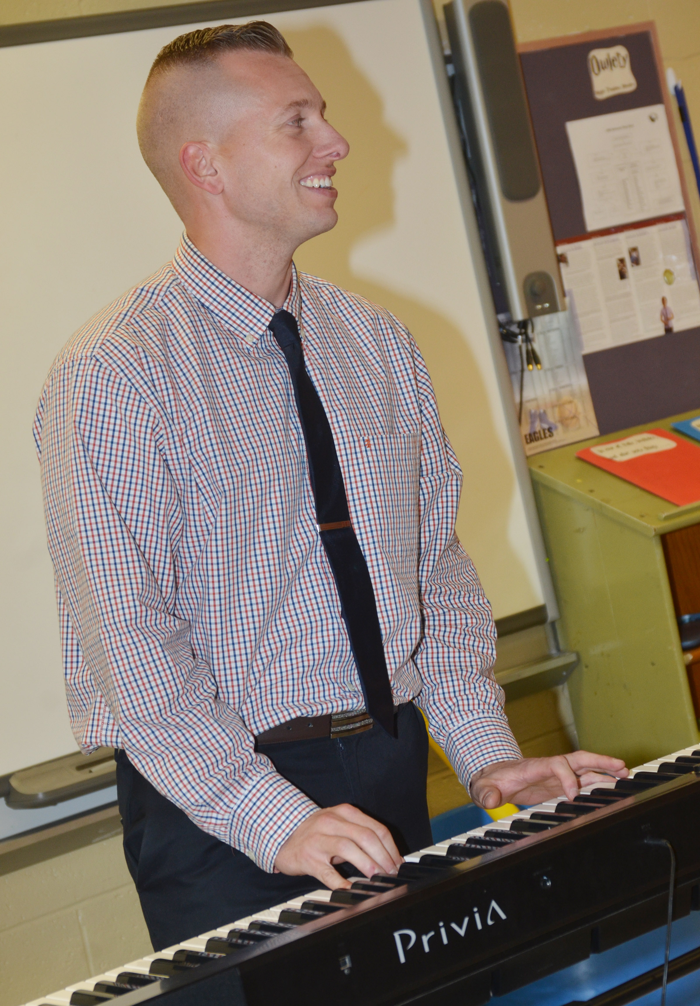 CMS Principal Zach Lewis plays the piano for his students.