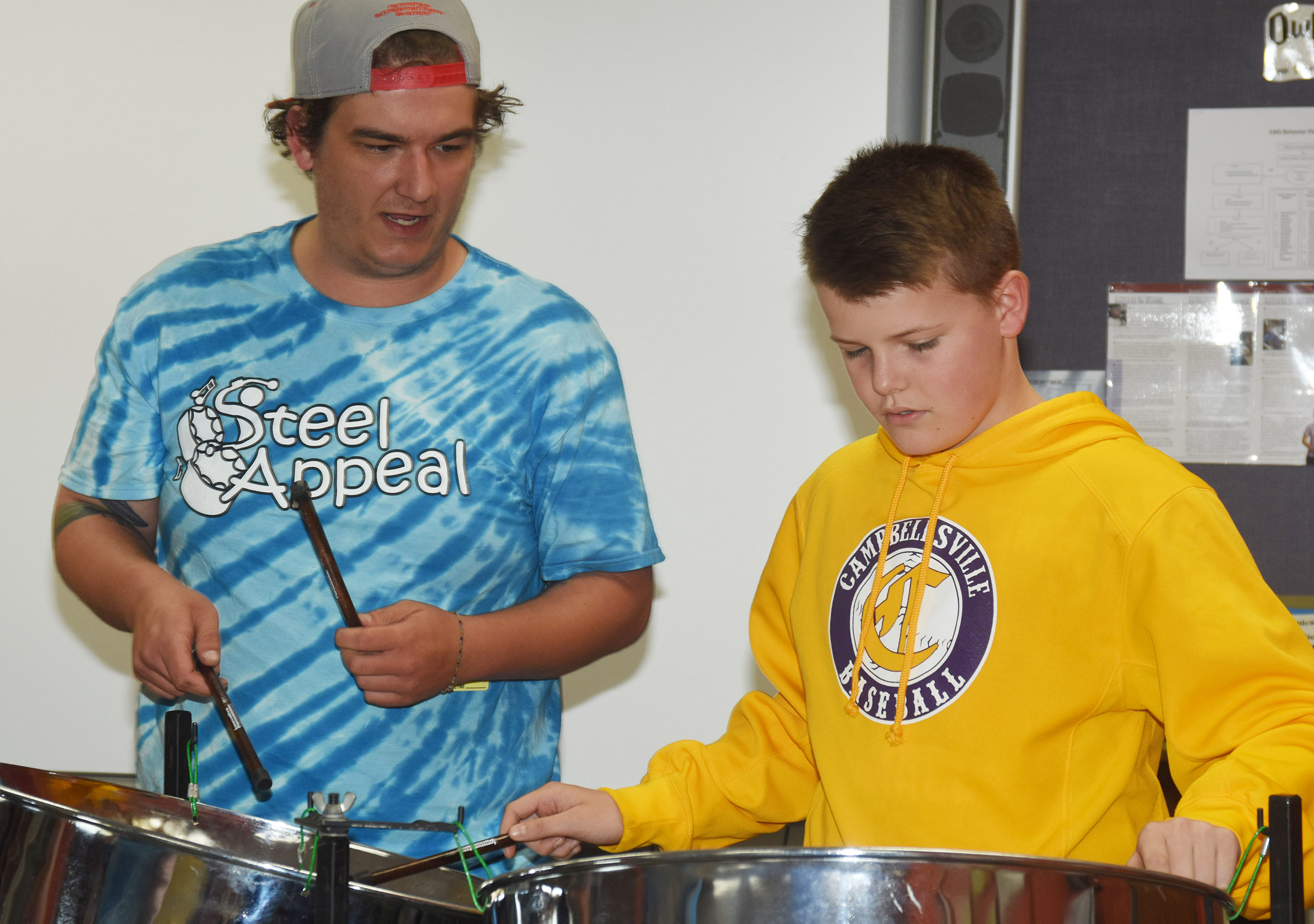 CU music students Jordan Hines helps seventh-grader Konner Forbis learn to play the steel drums.