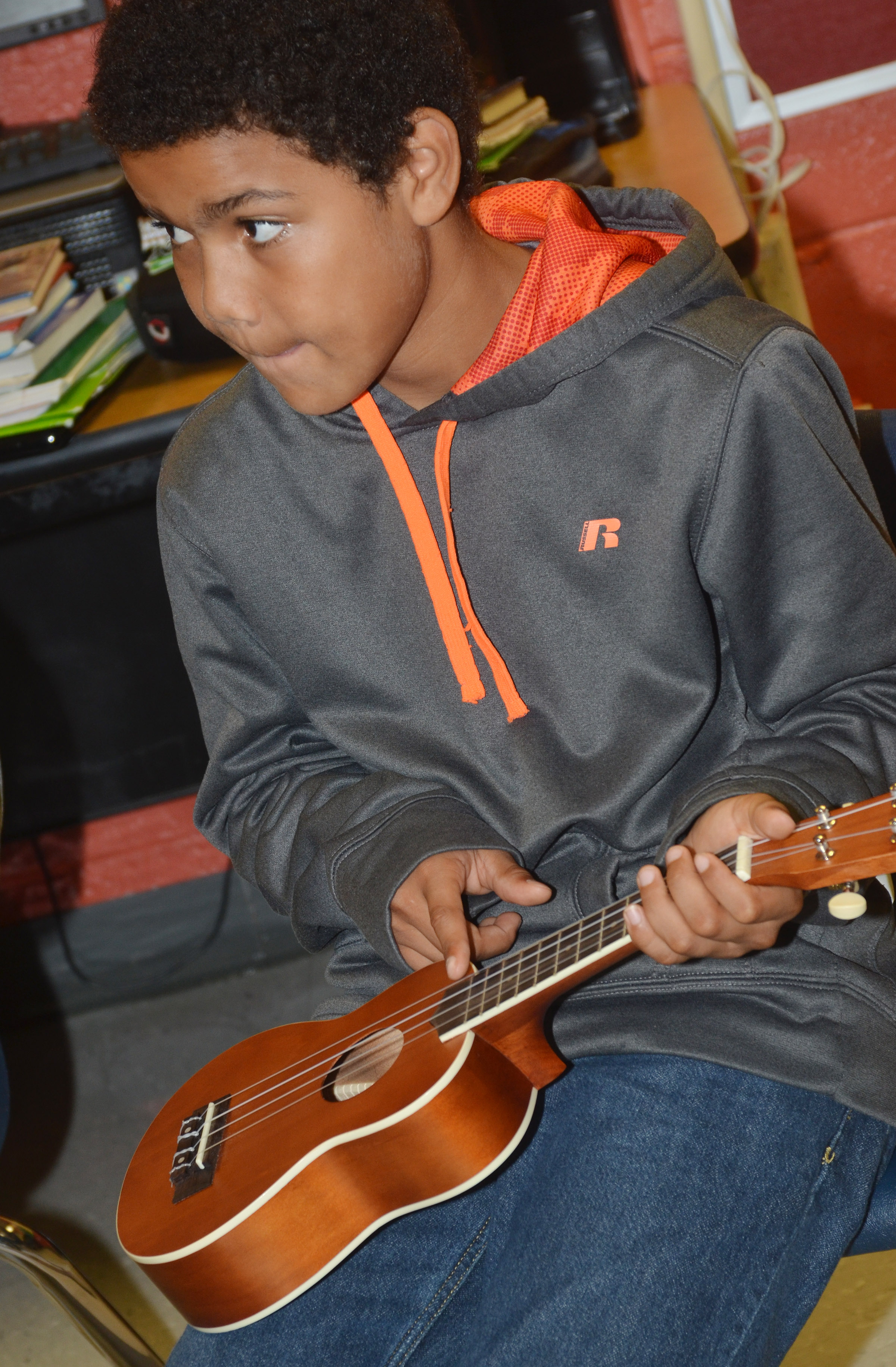 CMS sixth-grader Tashaun Hart strums the ukulele.