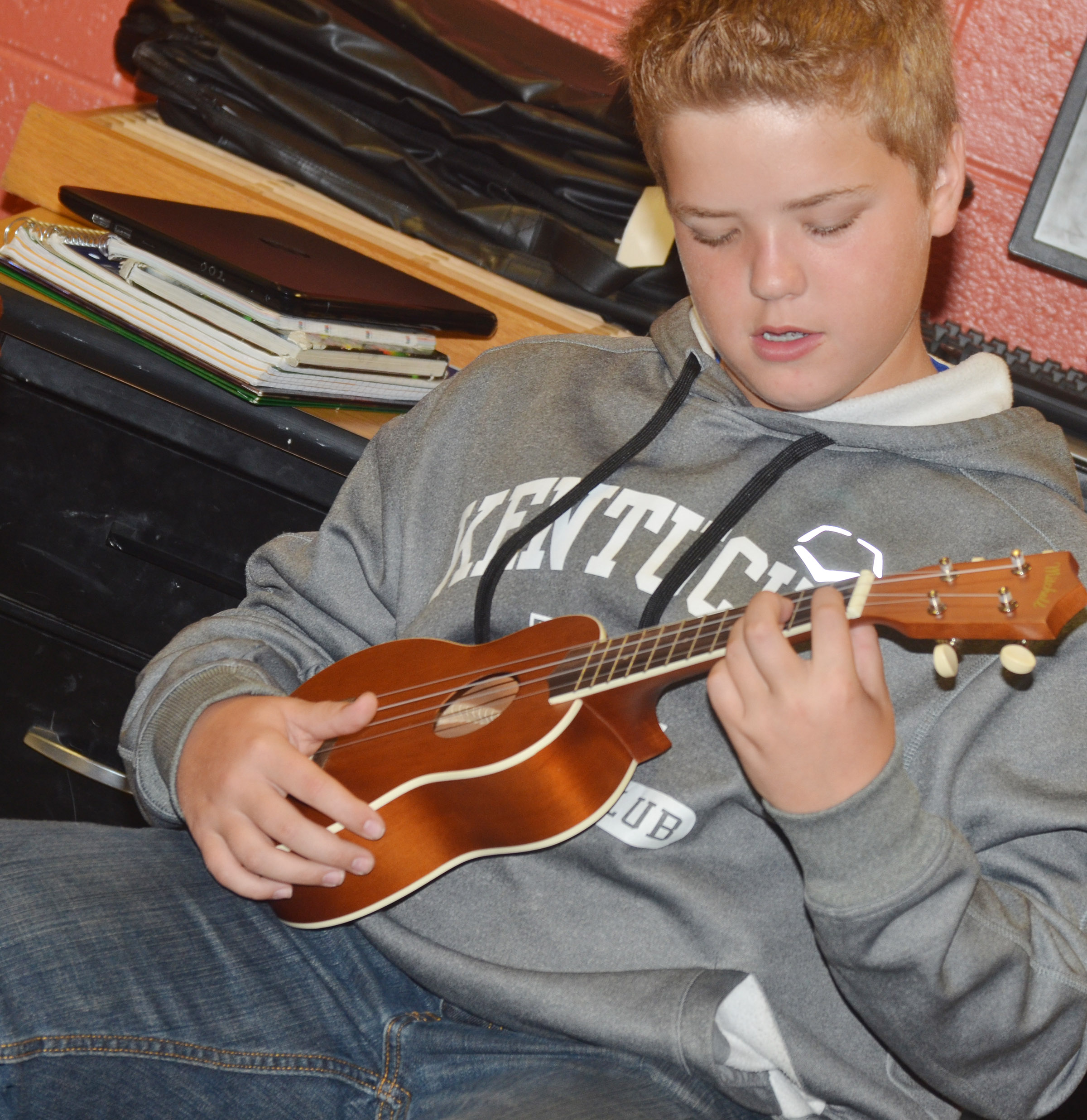 CMS sixth-grader Ryan Grubbs plays a chord on the ukulele.