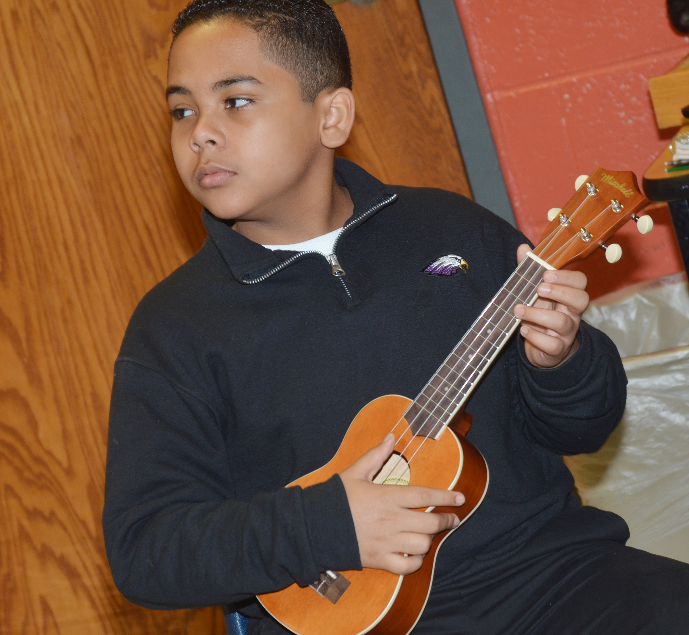 CMS sixth-grader Diego Noyola plays a chord on the ukulele.
