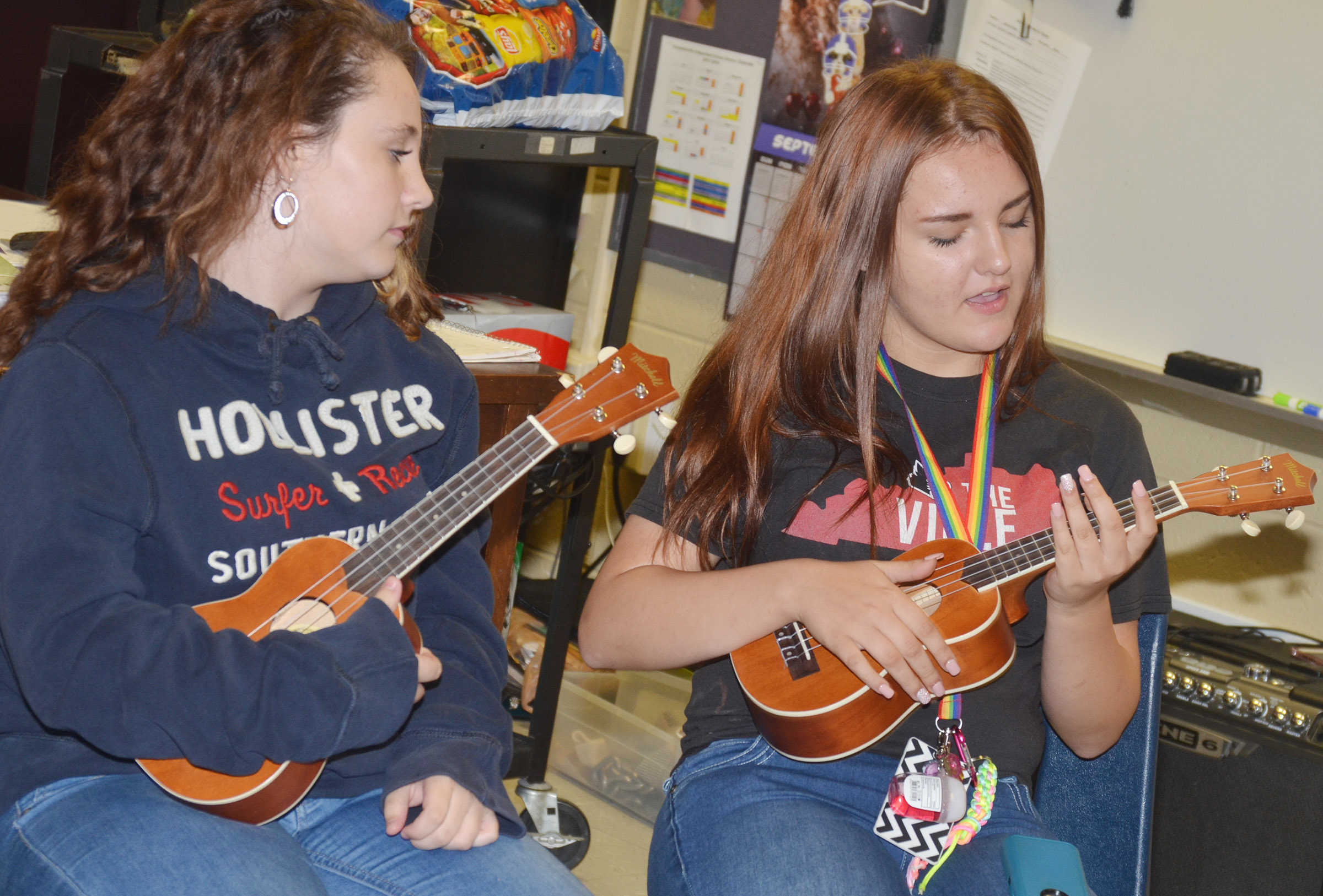 CMS eighth-grader Star Reed, at left, and seventh-grader Brooklyn Davis learn to play the ukulele.