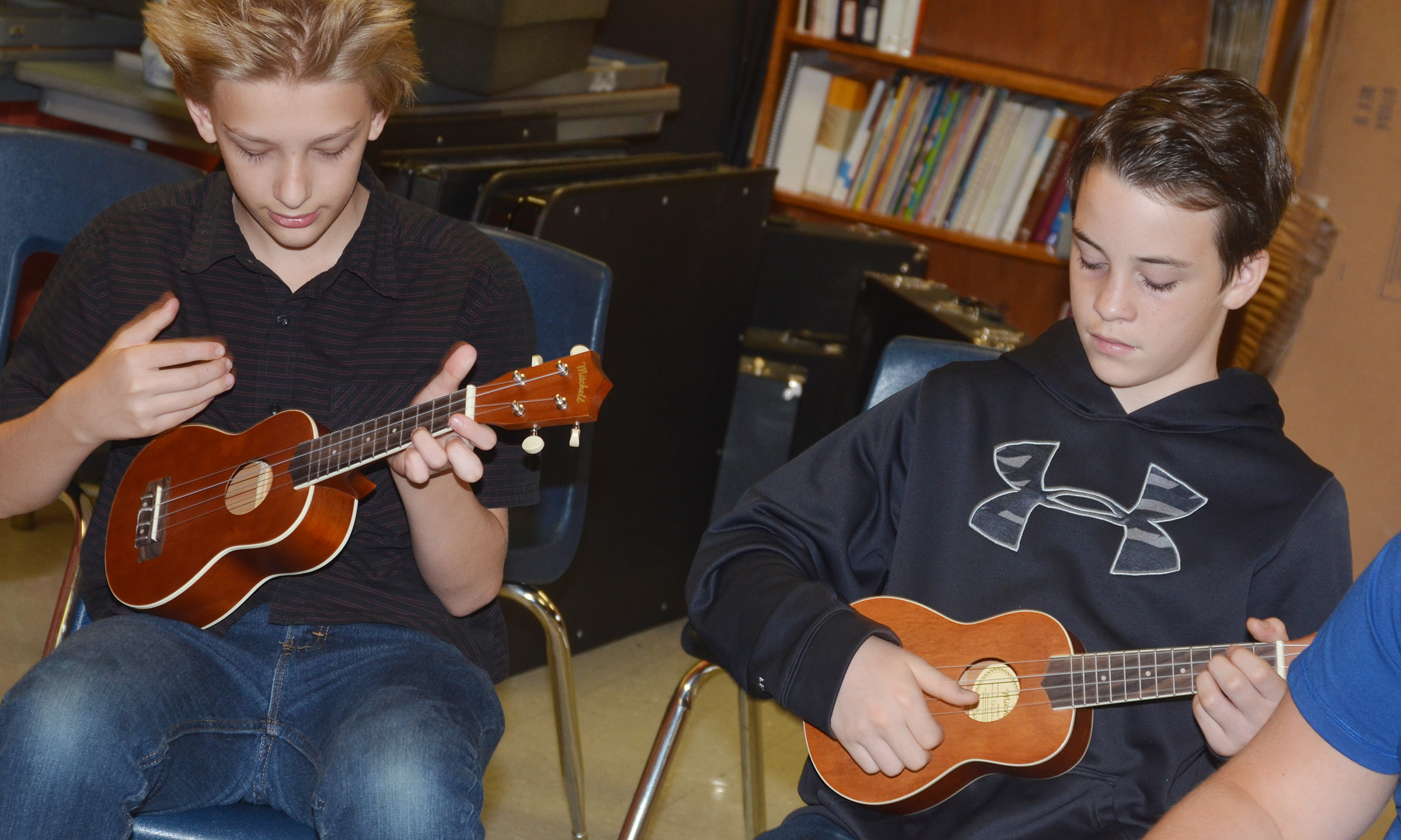 CMS sixth-grader Jacob Releford, at left, and seventh-grader Sean Mings strum the ukulele.