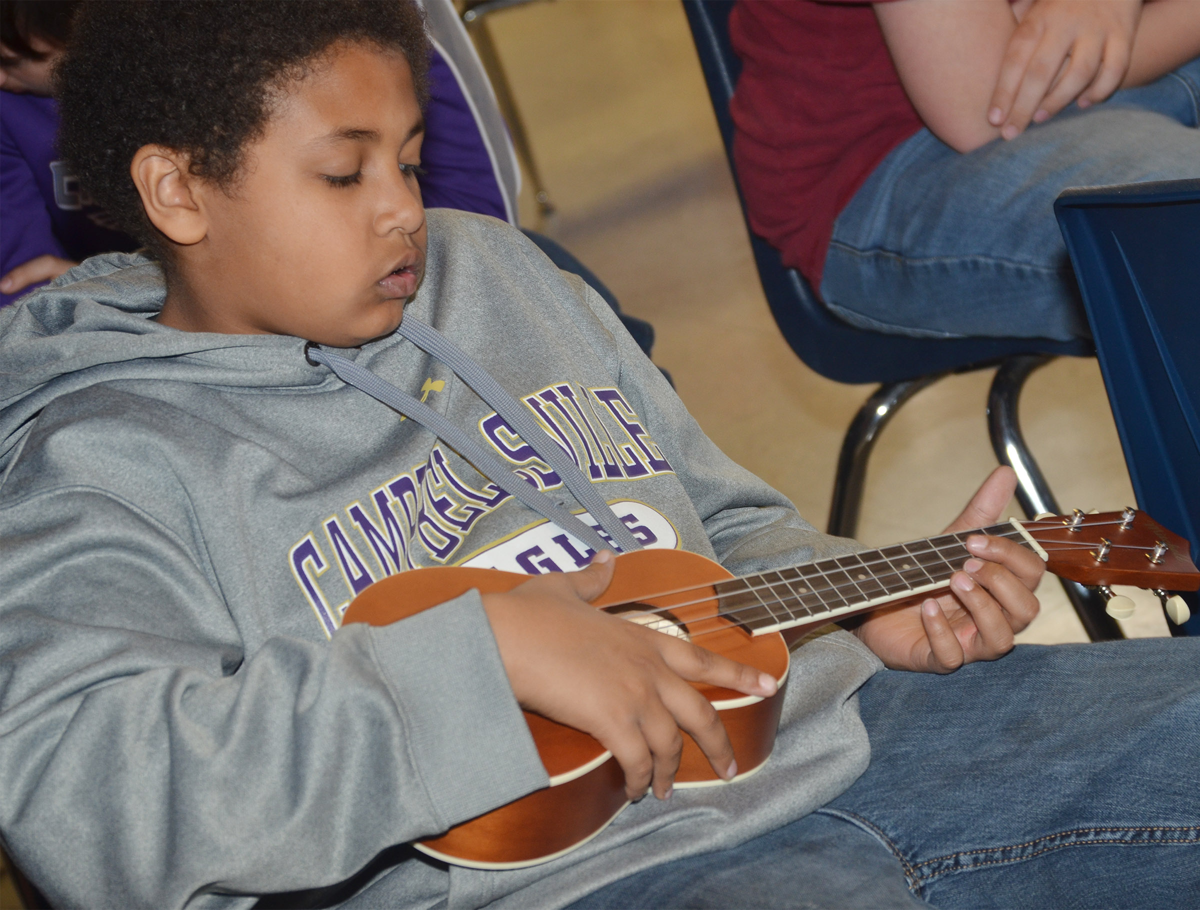 CMS sixth-grader Ronin Smith plays a chord on the ukulele.