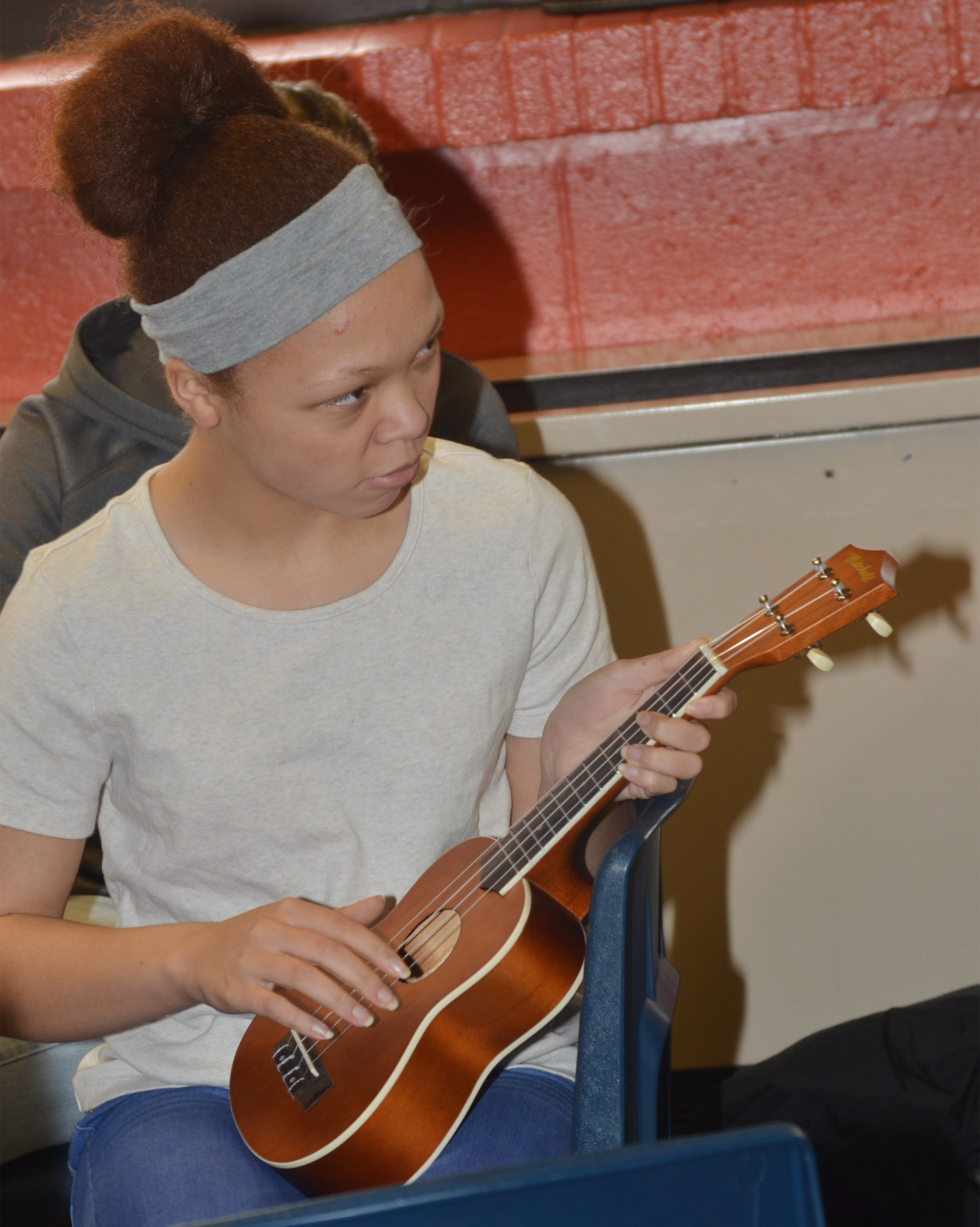 CMS seventh-grader Kitana Taylor plays a chord on the ukulele.