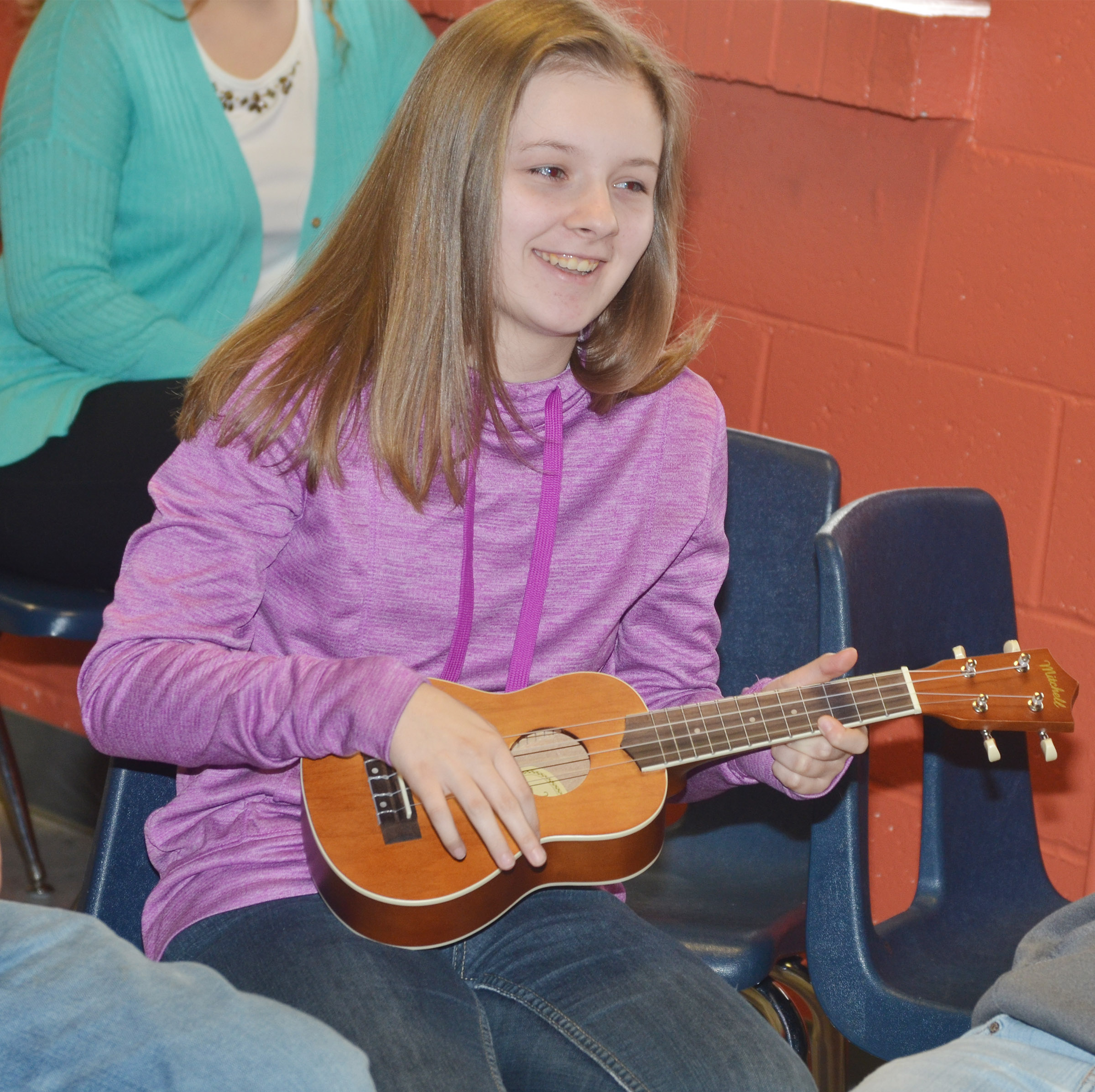 CMS seventh-grader Serenity Ford plays a chord on the ukulele.