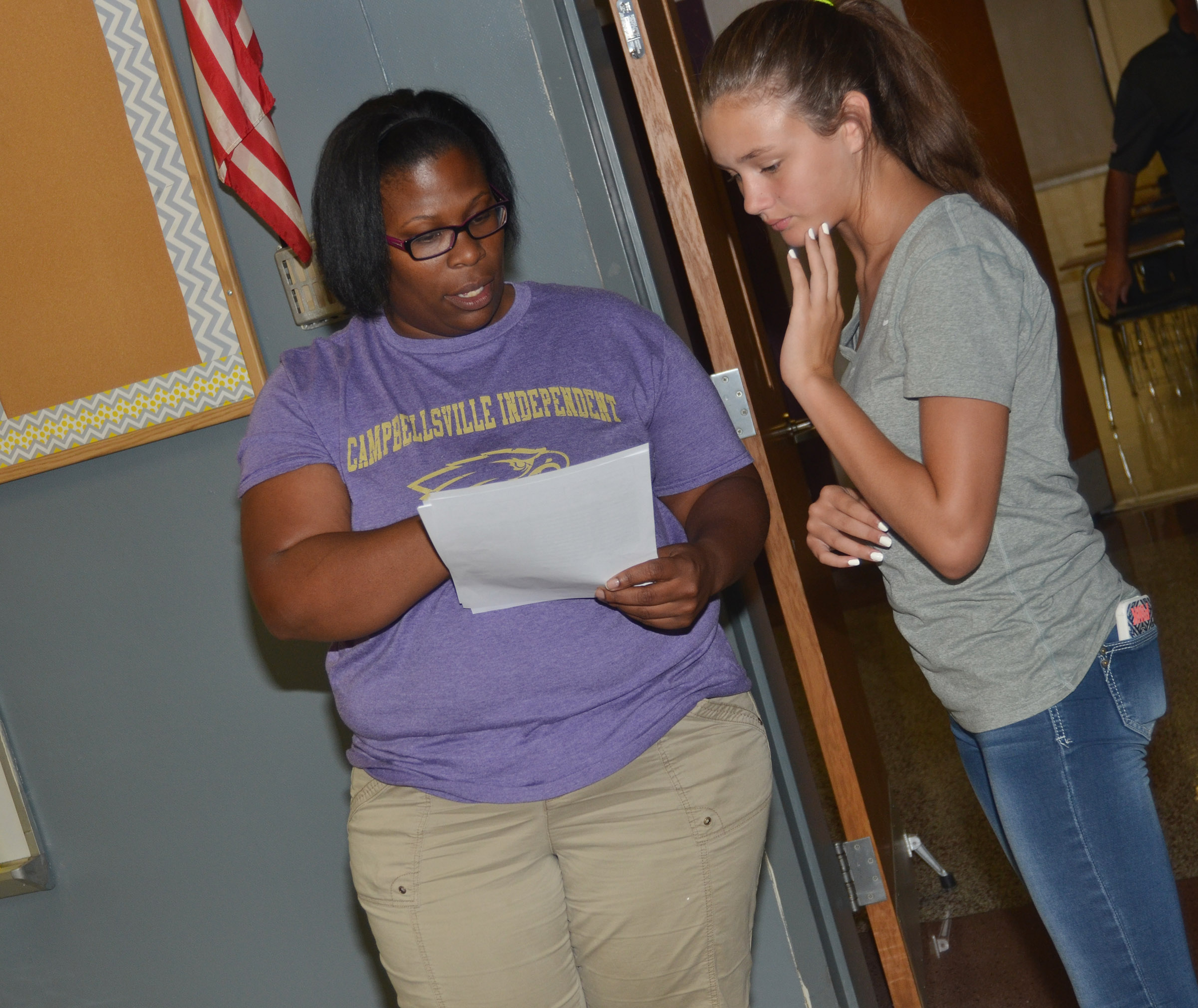 CMS teacher Tiarra Cecil looks over seventh-grader Haylee Allen's schedule.