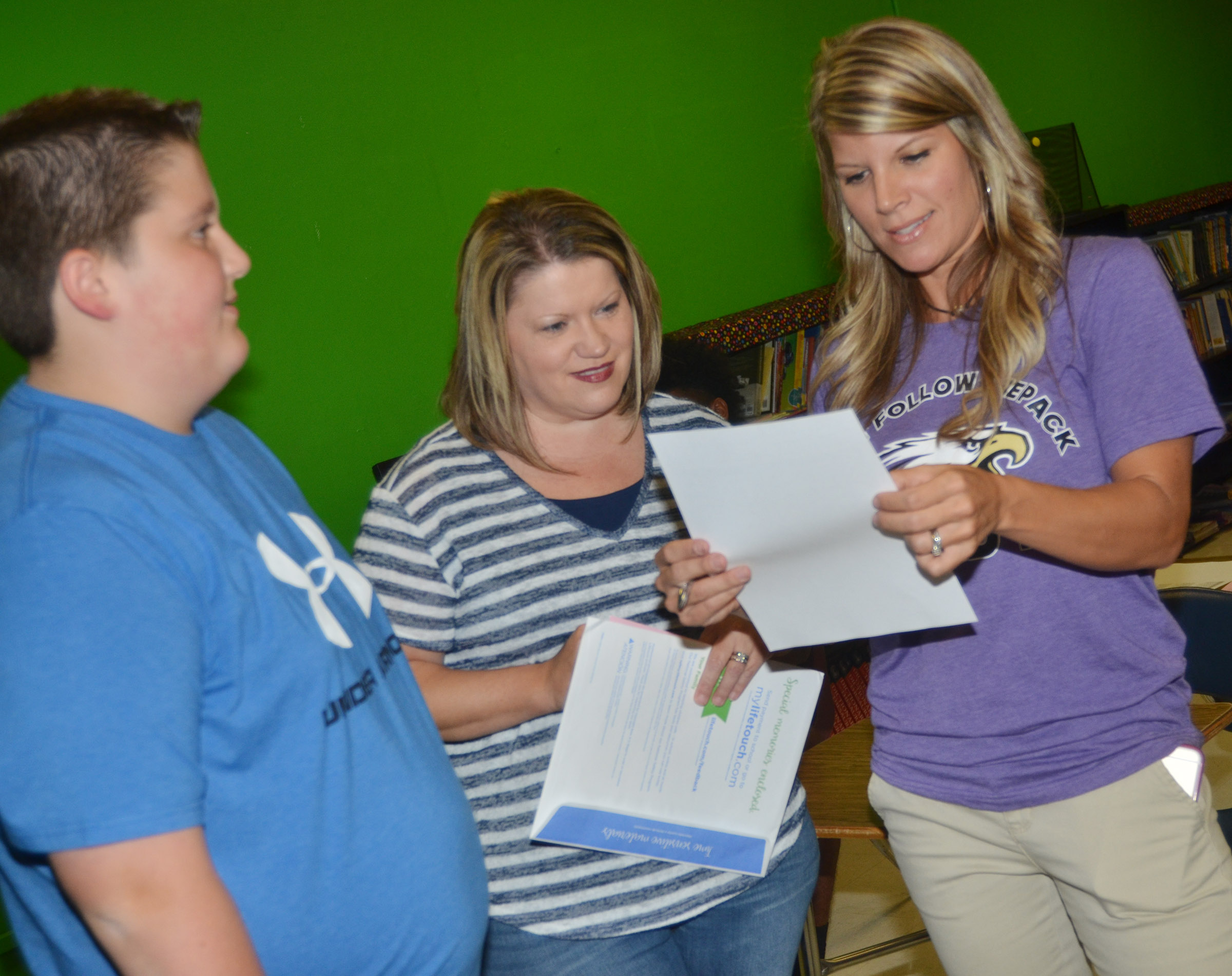CMS teacher Andrea Gribbins looks over Luke McDonald's schedule with his mother Stephanie.