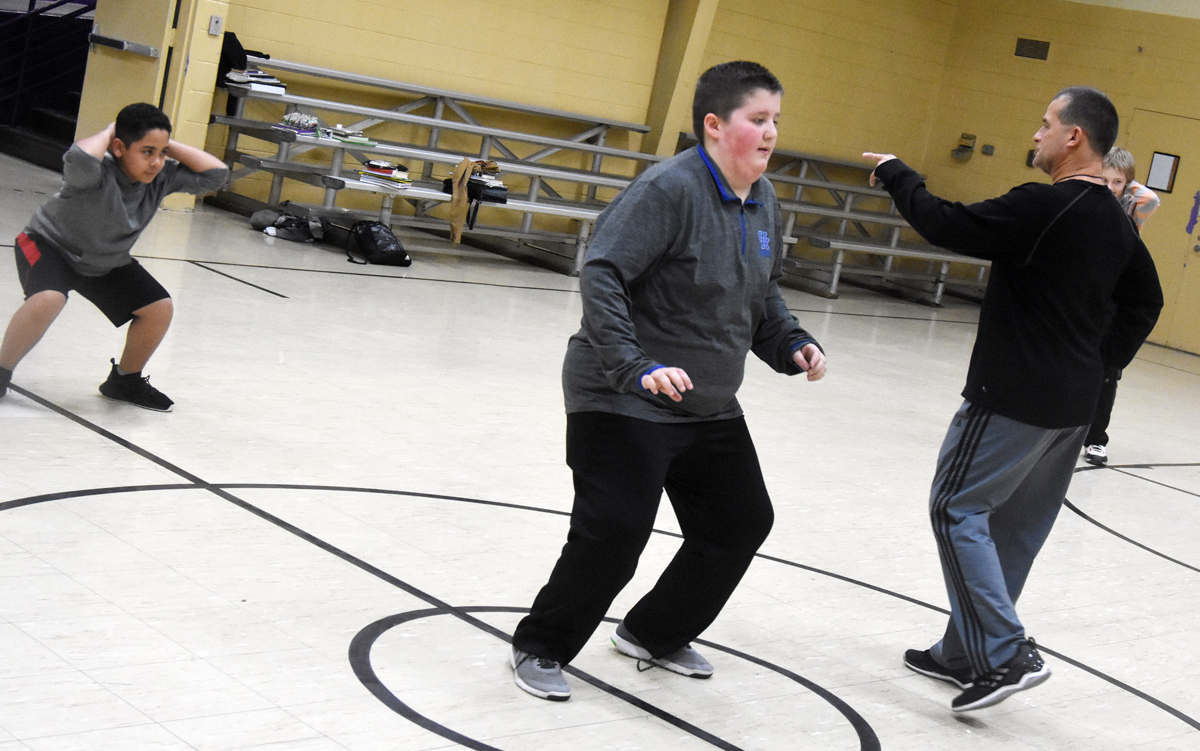 CMS substitute teacher Lynn Kearney leads students in a warmup exercise. From left are sixth-graders Diego Noyola and Luke McDonald.