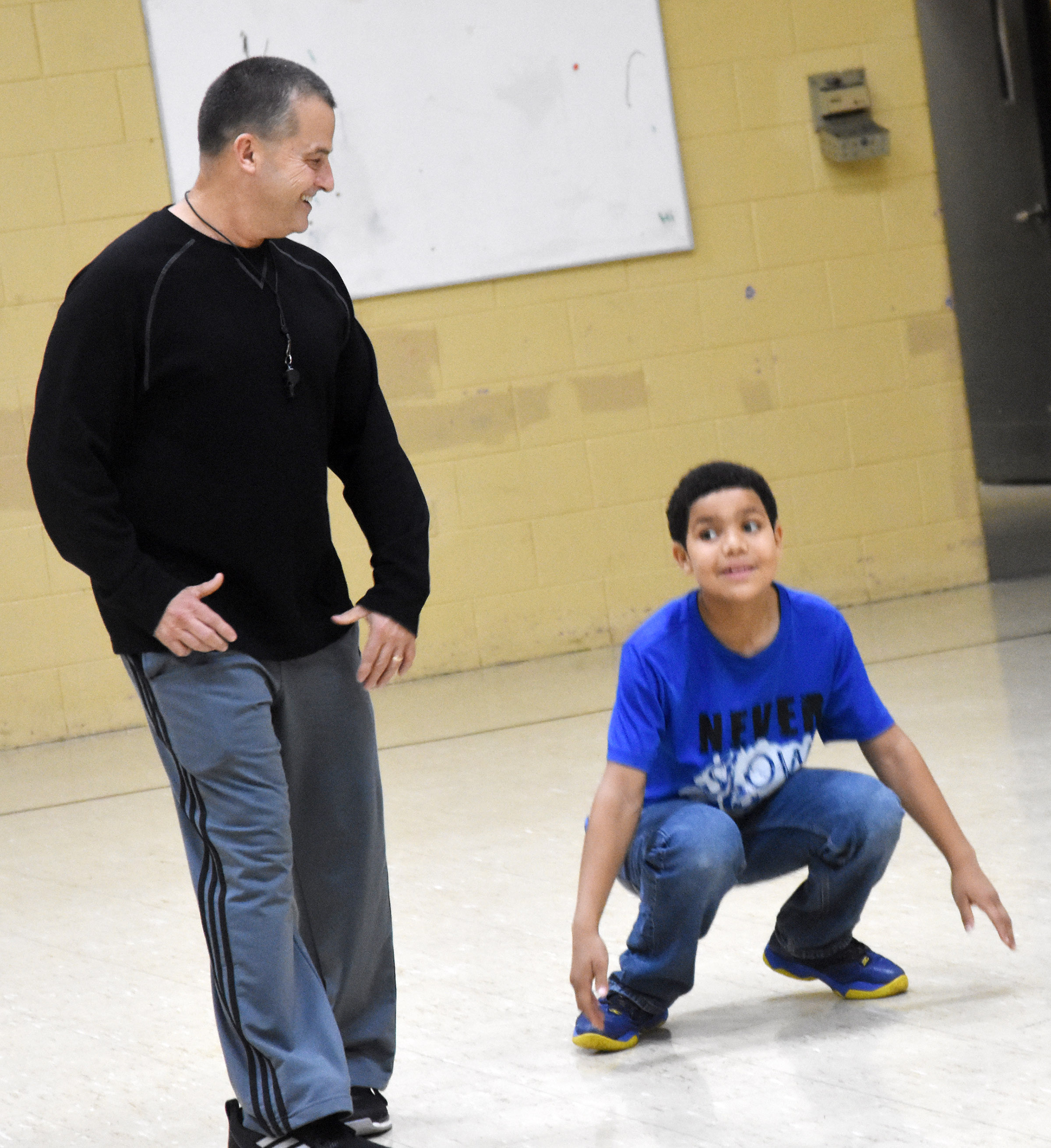 CMS substitute teacher Lynn Kearney leads sixth-grader Tashaun Hart in a warmup exercise.