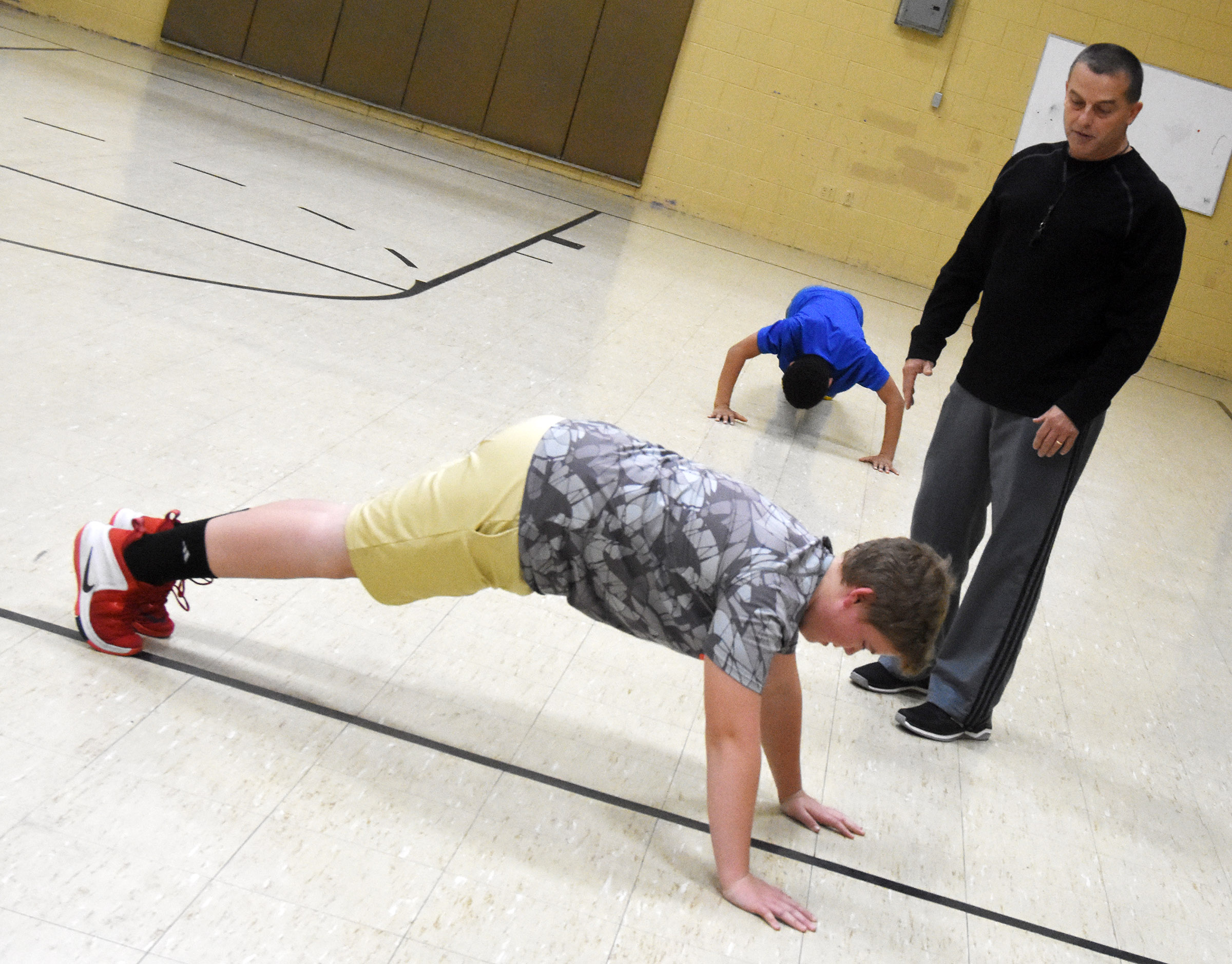 CMS substitute teacher Lynn Kearney leads students in a warmup exercise. From left are sixth-graders Ryan Grubbs and Tashaun Hart.