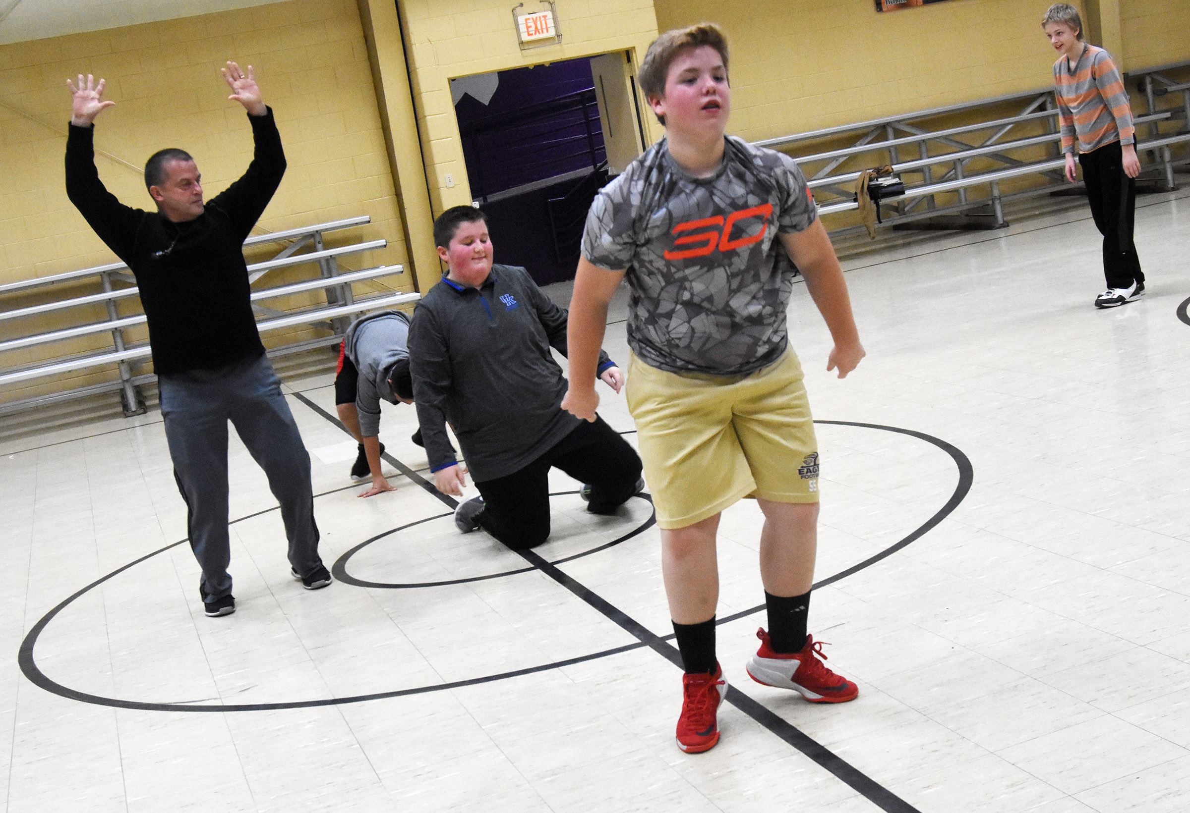 CMS substitute teacher Lynn Kearney leads students in a warmup exercise. From left are sixth-graders Luke McDonald, Ryan Grubbs and Jacob Releford.
